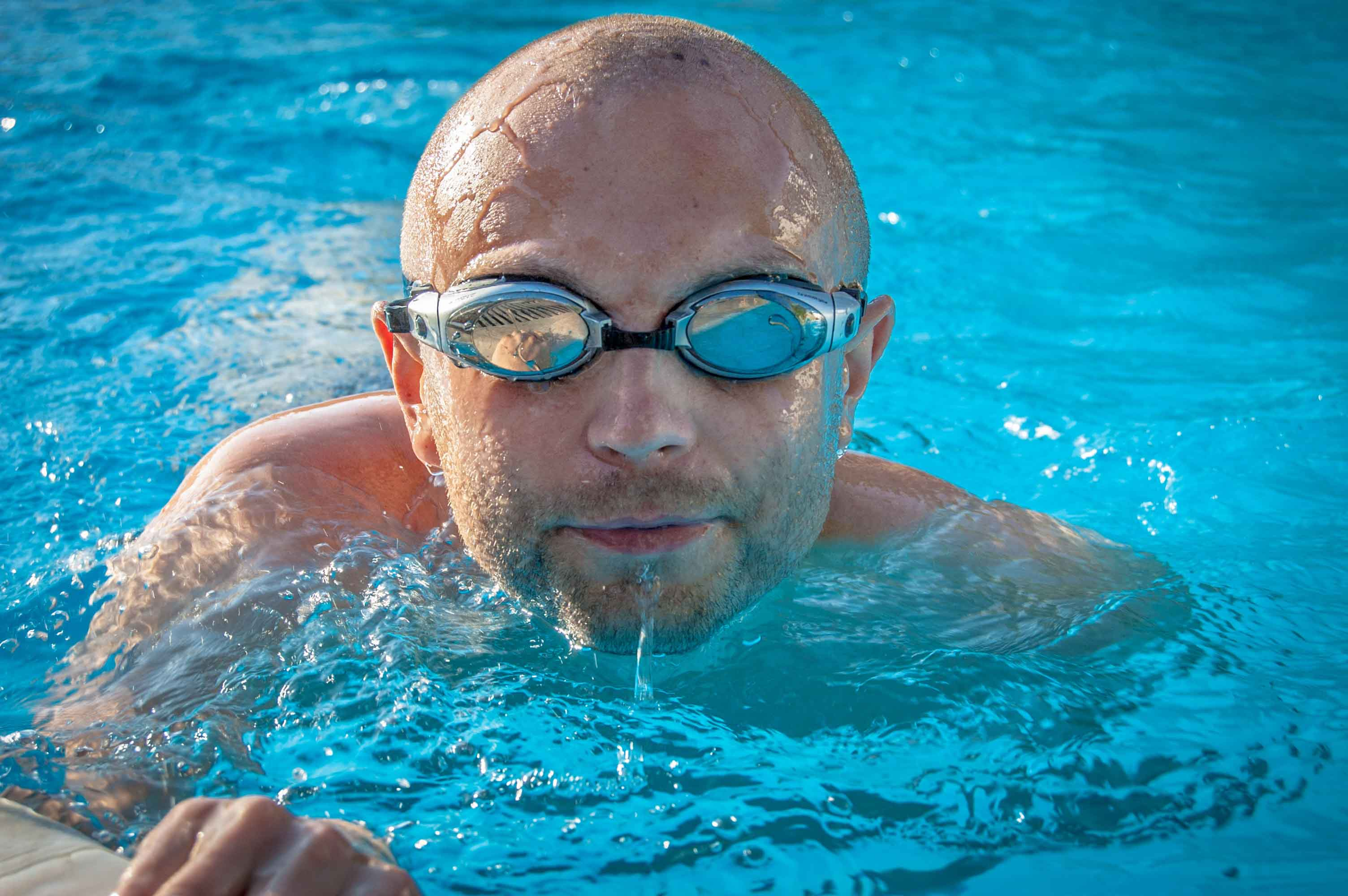 Chico con gafas nadando en piscina
