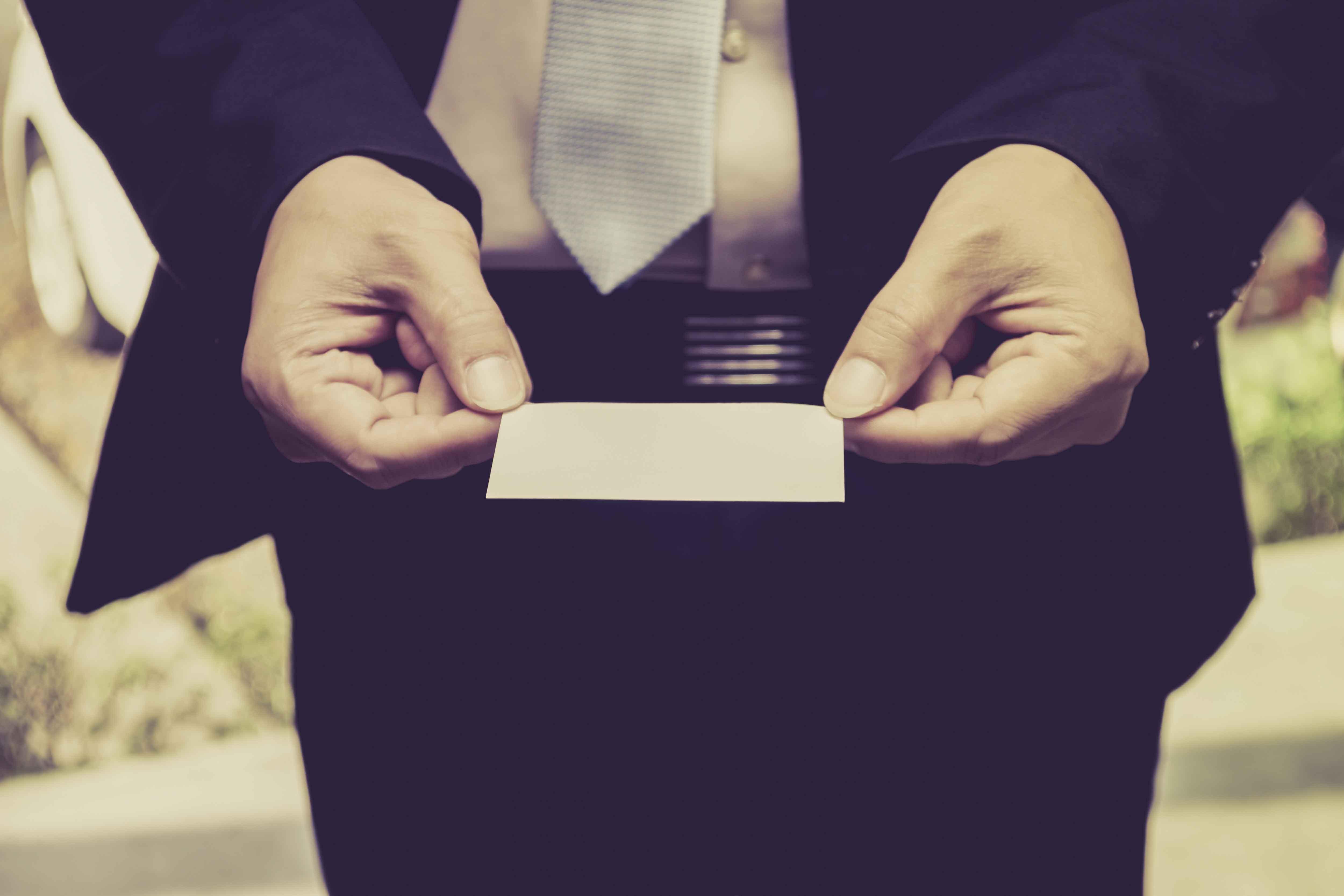 Señor trajeando sujetando tarjeta de visita en blanco