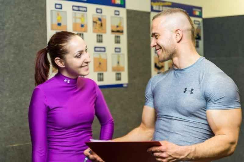 chico asesorando a chica en gimnasio