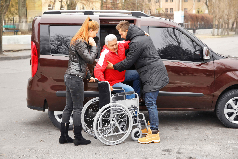 Chico y chica bajando a un señor dependiente del coche a la silla de ruedas