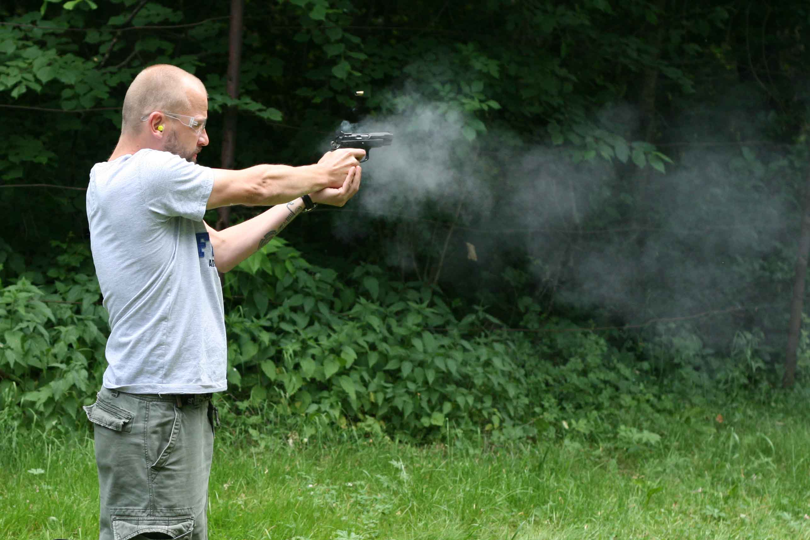 Hombre disparando en un paisaje verde