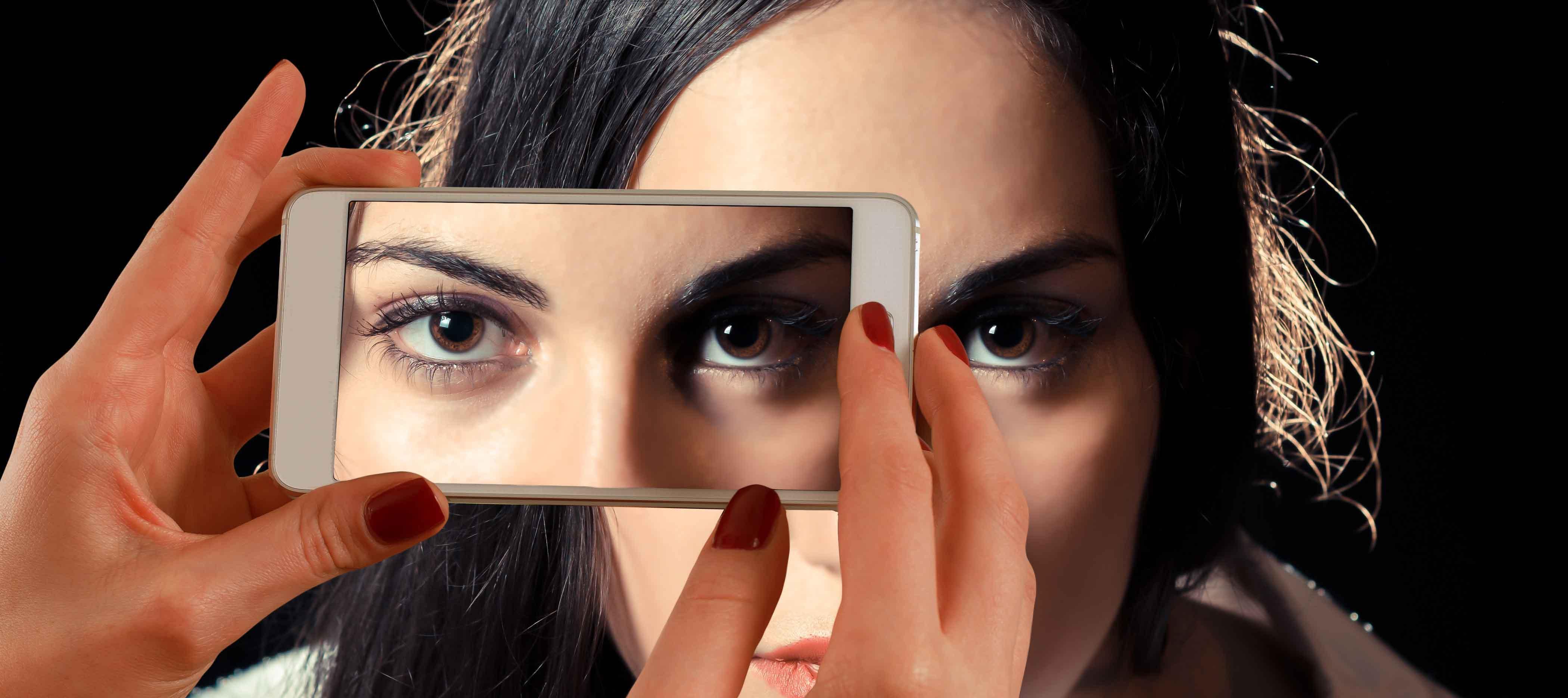 Imagen simbólica de chica a la que le están tomando una foto de la mirada con un móvil
