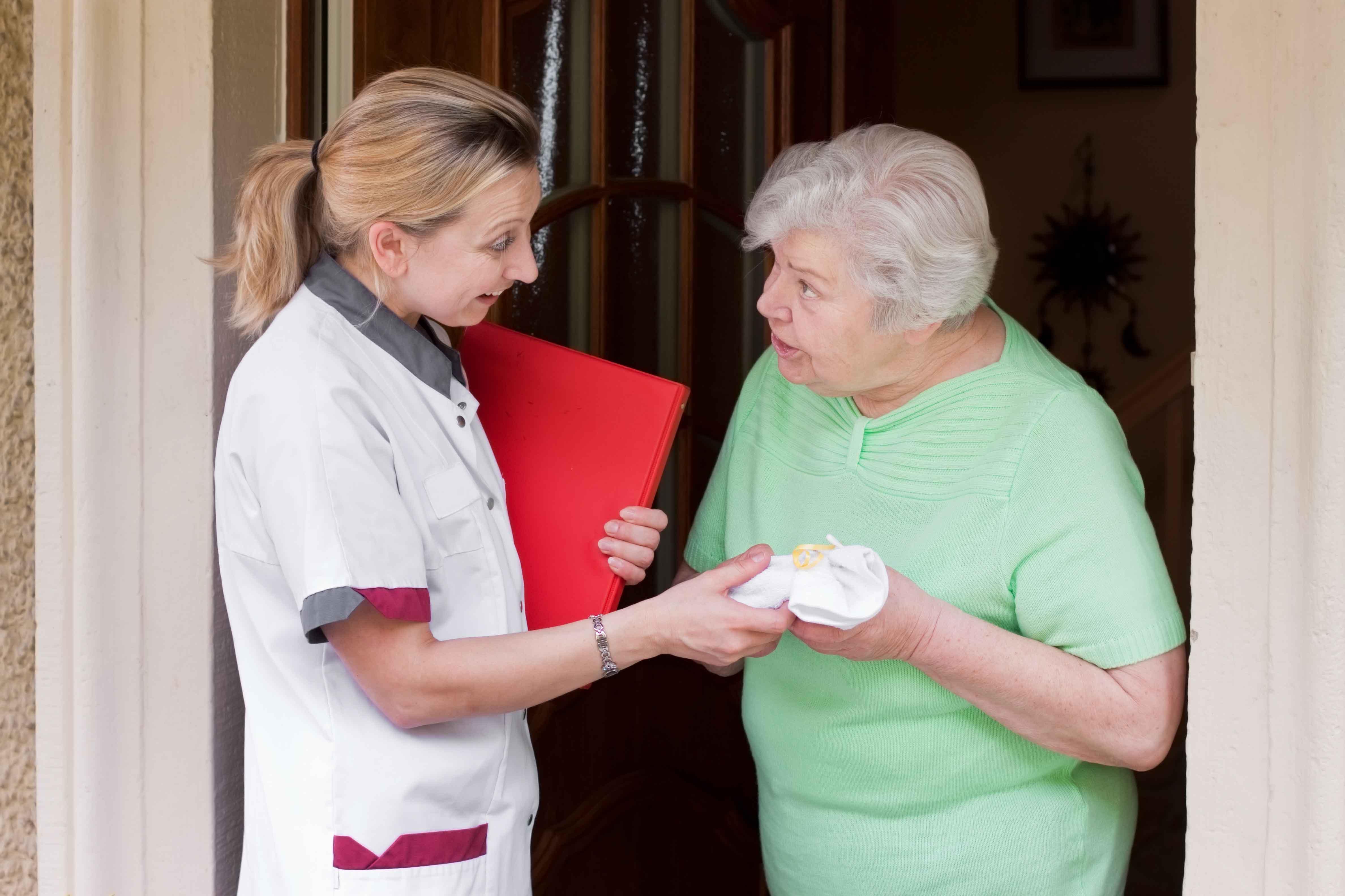 Auxiliar saludando a persona mayor