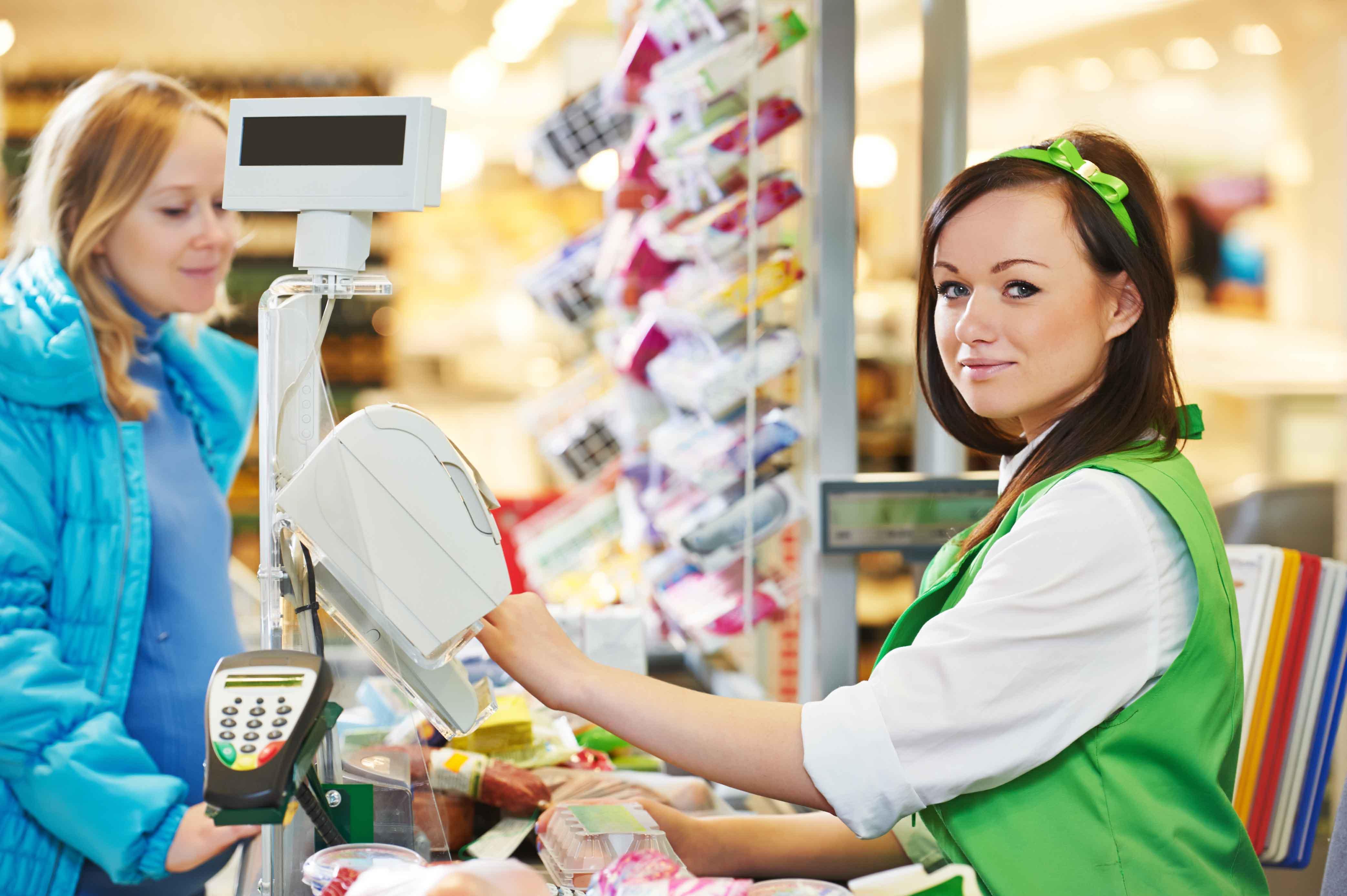 Chica cobrando a señora en supermercado