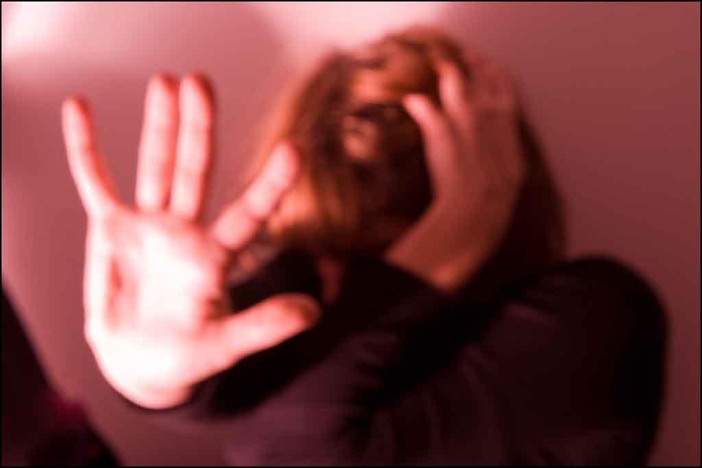 """Chica haciendo símbolo de """"stop"""" con la mano"""
