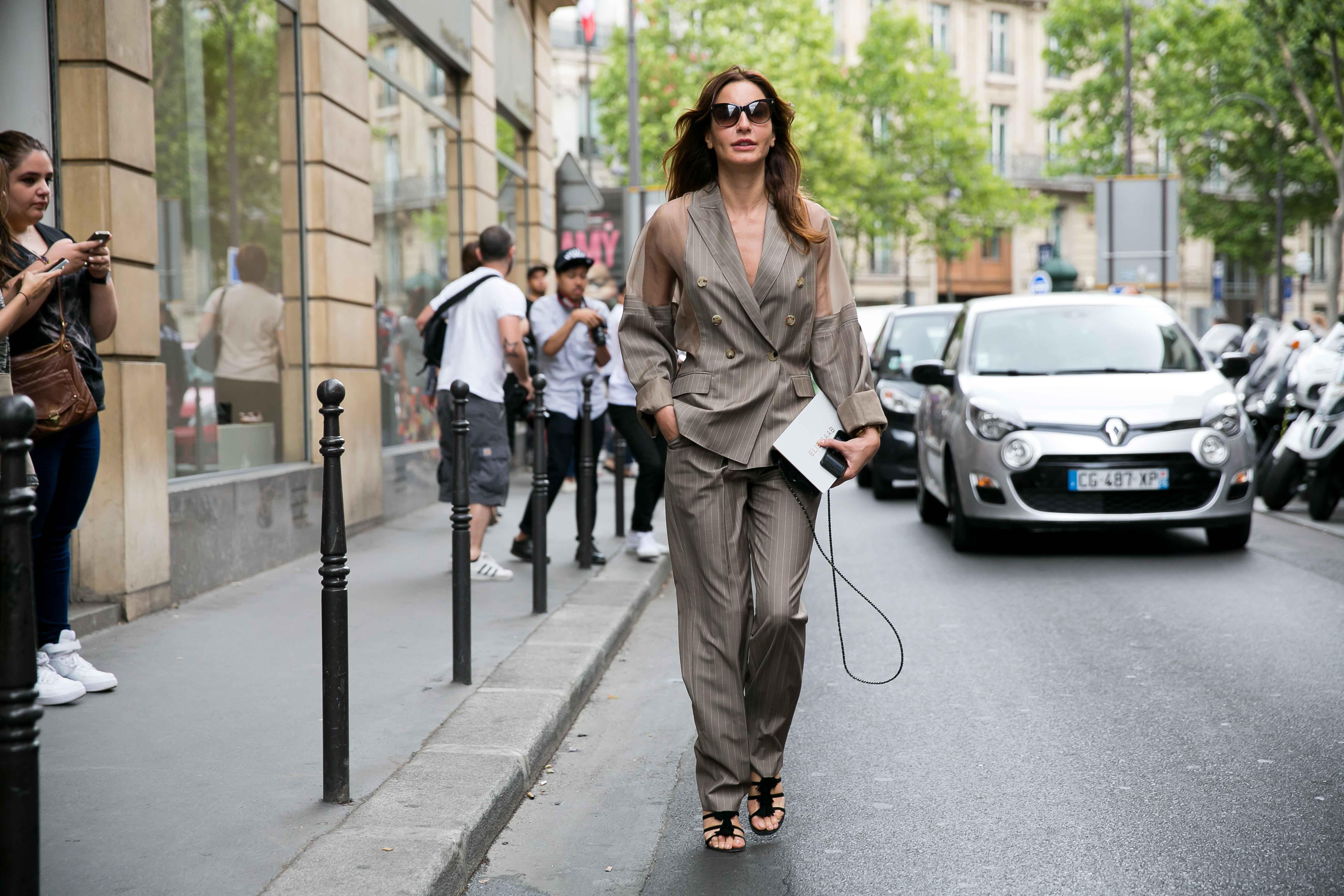 Chica muy bien vestida caminando por la calle