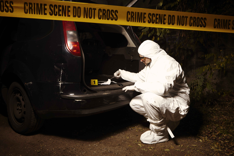 Investigador examinando pruebas en el maletero de un coche de escena de crimen