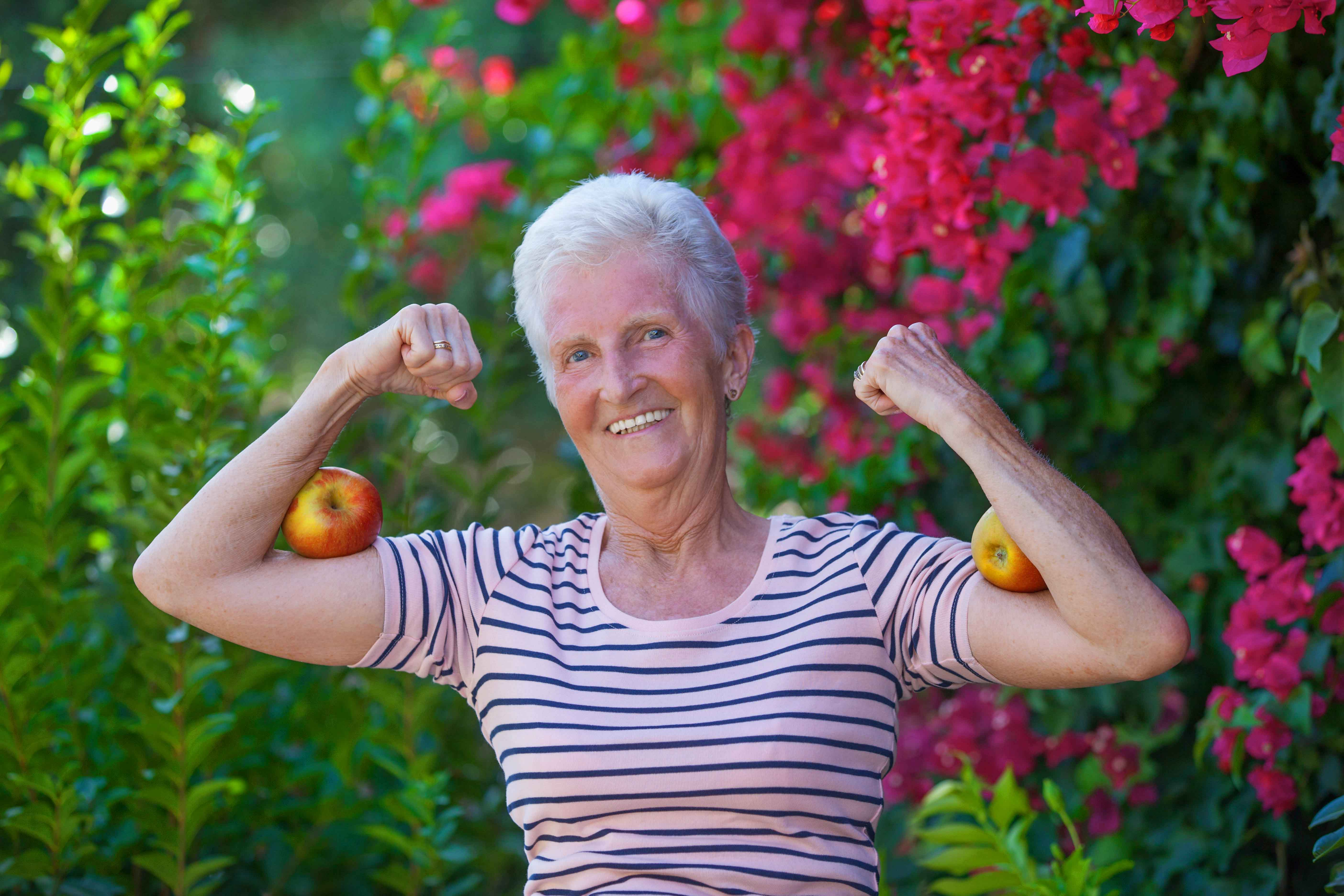 Anciana con dos manzanas en bíceps