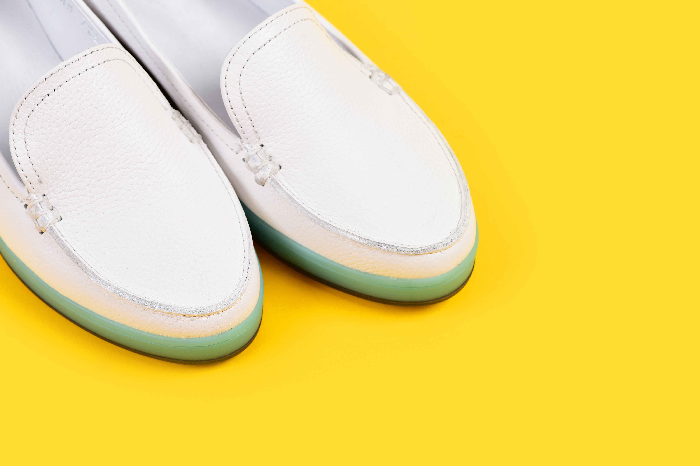 Zapatos blancos sobre fondo amarillo