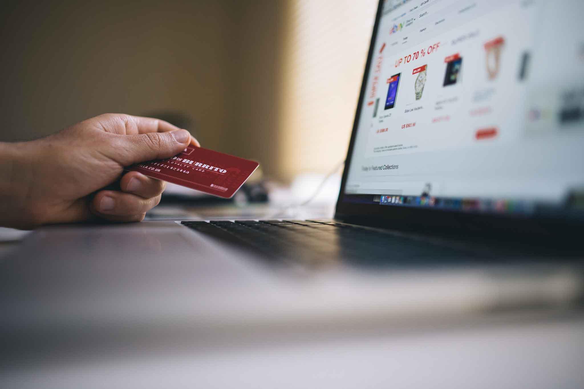 Persona ante un portátil con tarjeta de crédito en la mano