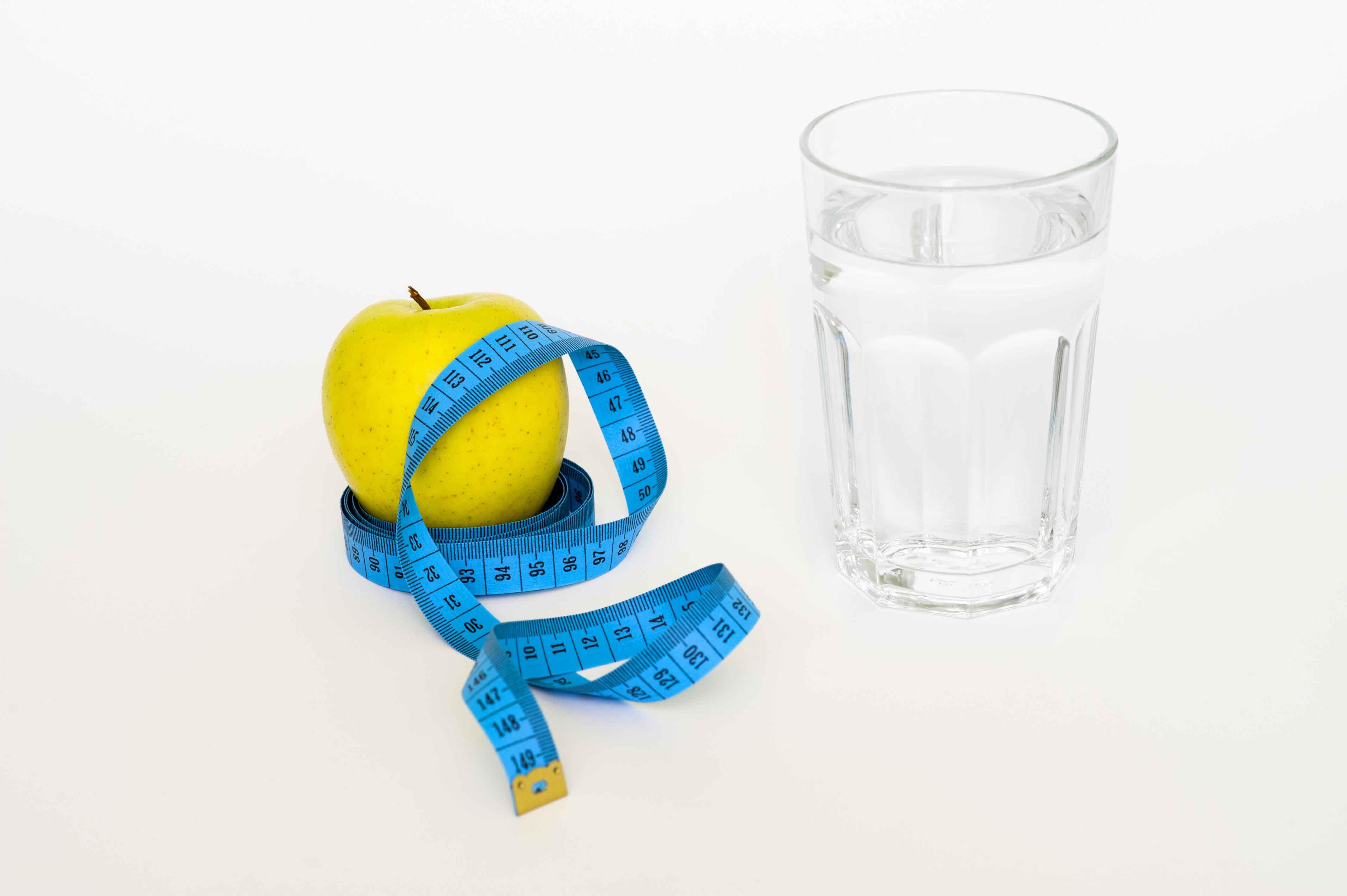 Manzana con cinta métrica alrededor y vaso de agua al lado