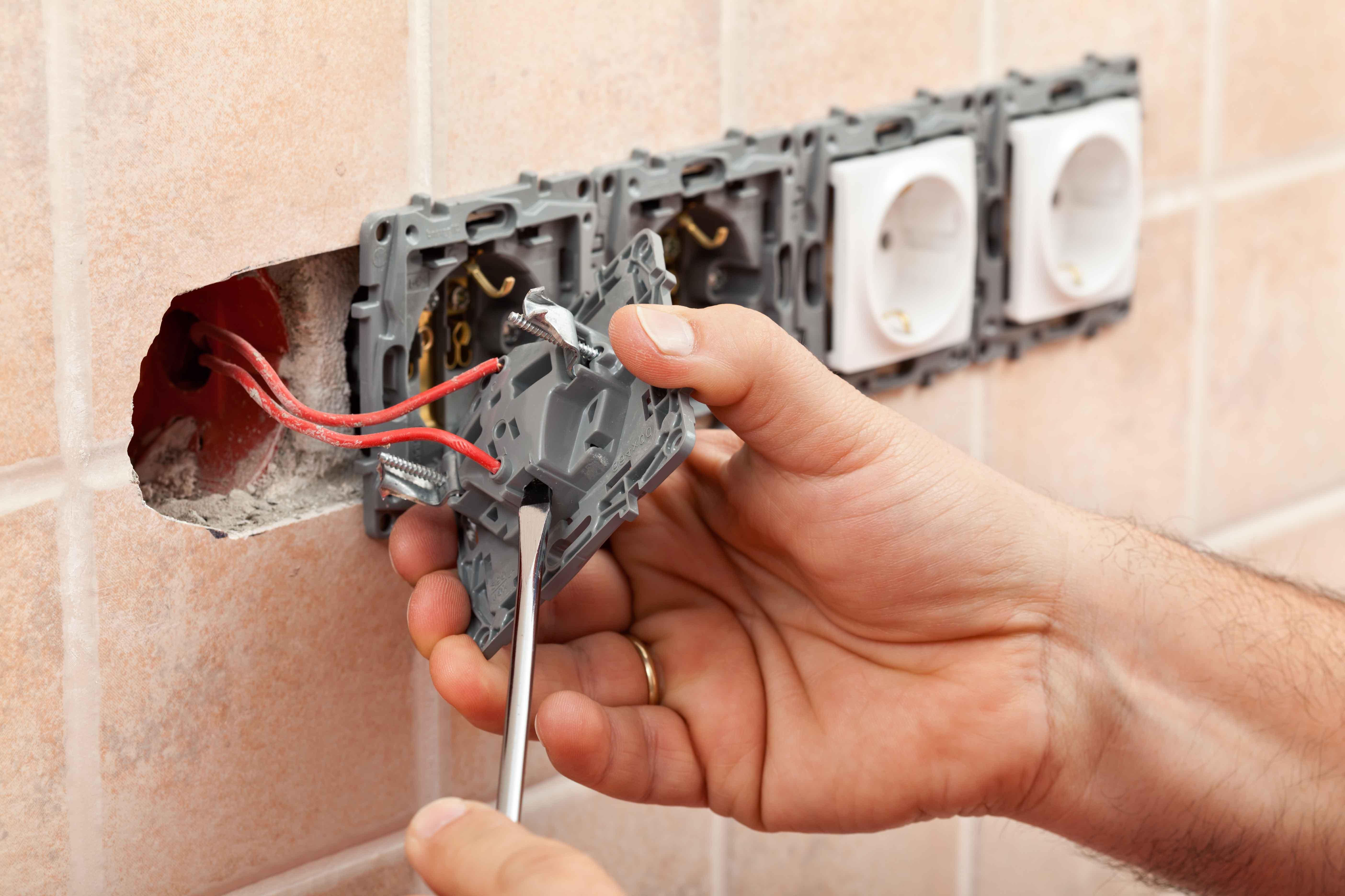 Electricista trabajando en toma de corriente