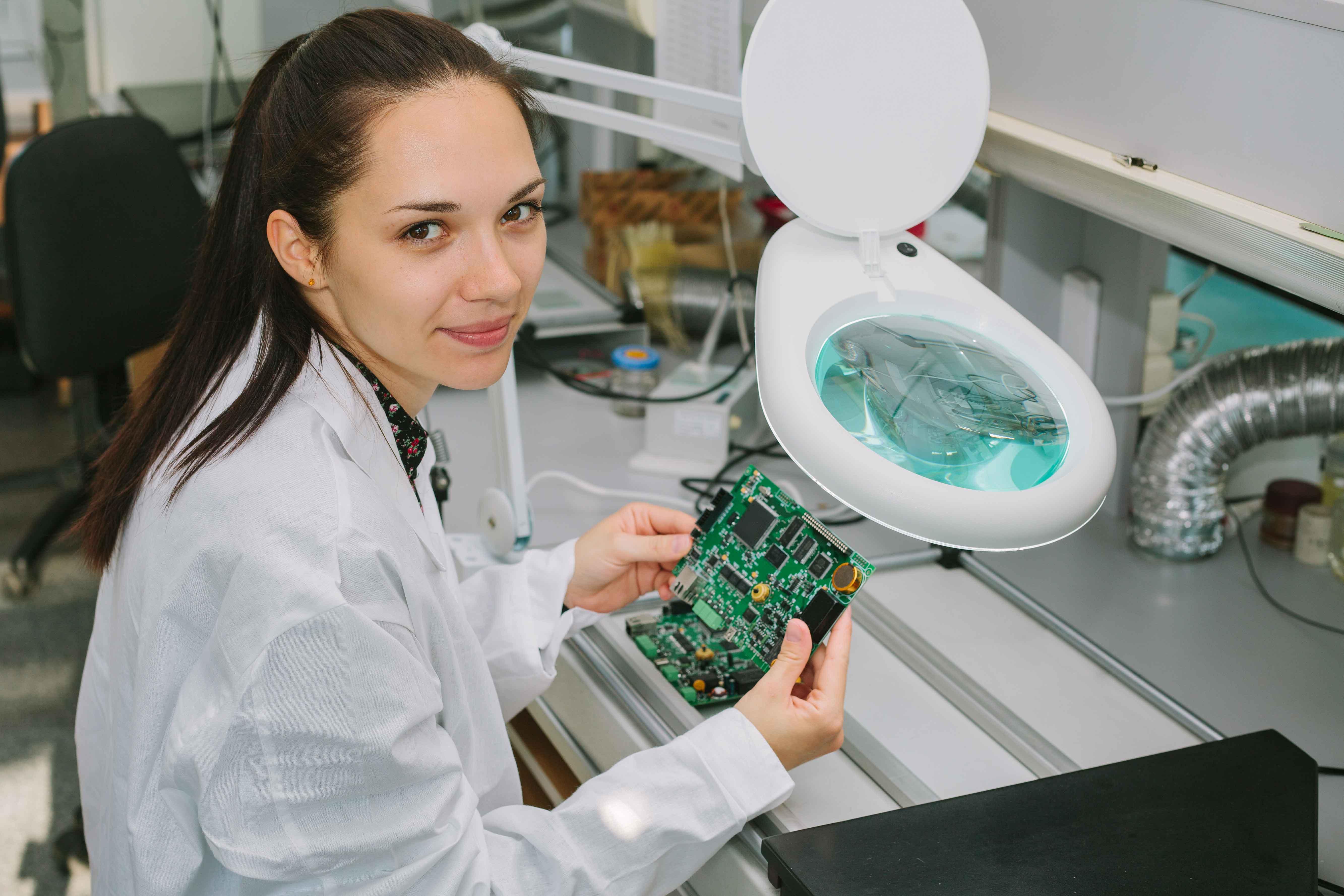 chica trabajando sobre placa electrónica