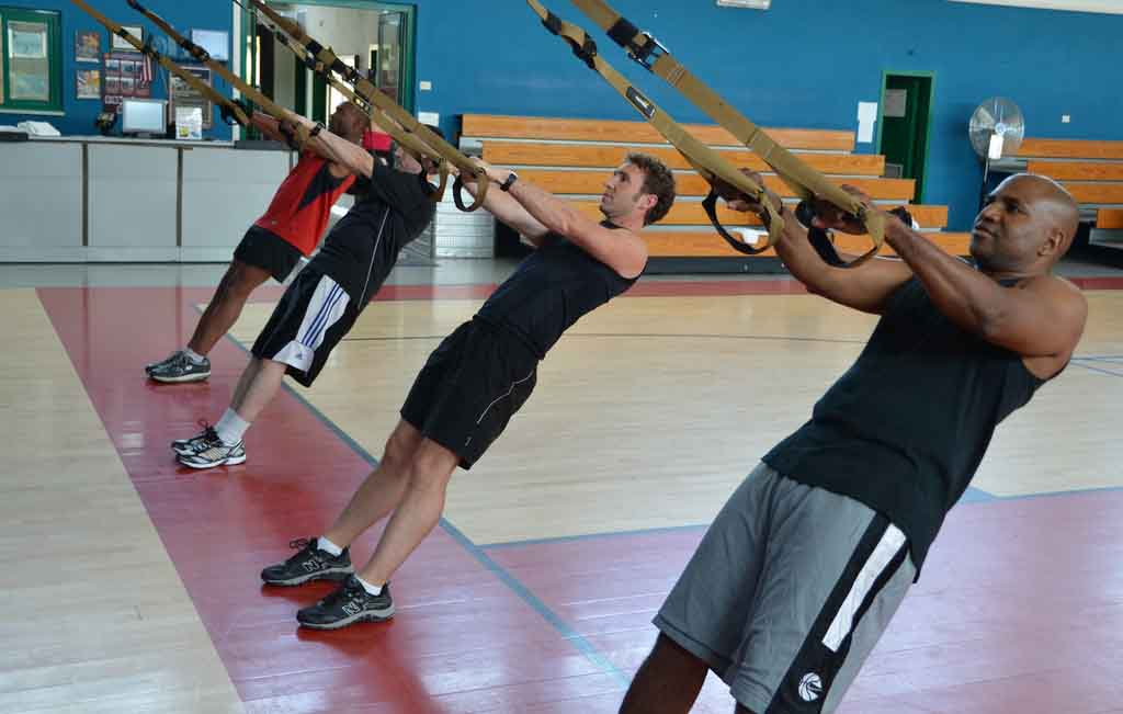 Tres personas entrenando con cintas TRX