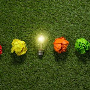 Foto de bombilla y bolas de papel de colores sobre un césped