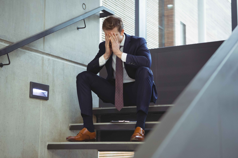 Chico ejecutivo sentado en escaleras disgustado