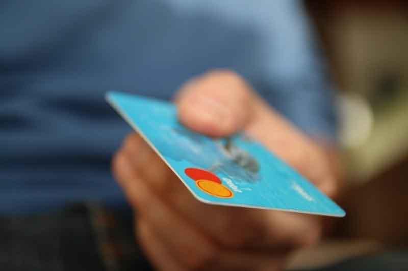 Persona con tarjeta bancaria en la mano