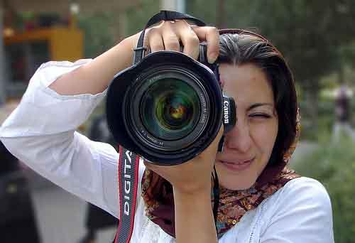 Chica sacando foto con cámara profesional