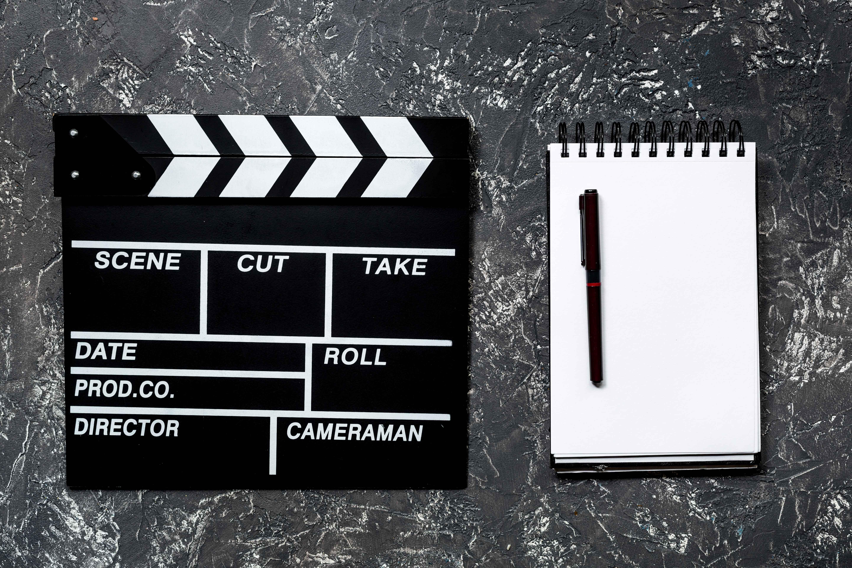 Claqueta de cine y libreta en blanco al lado
