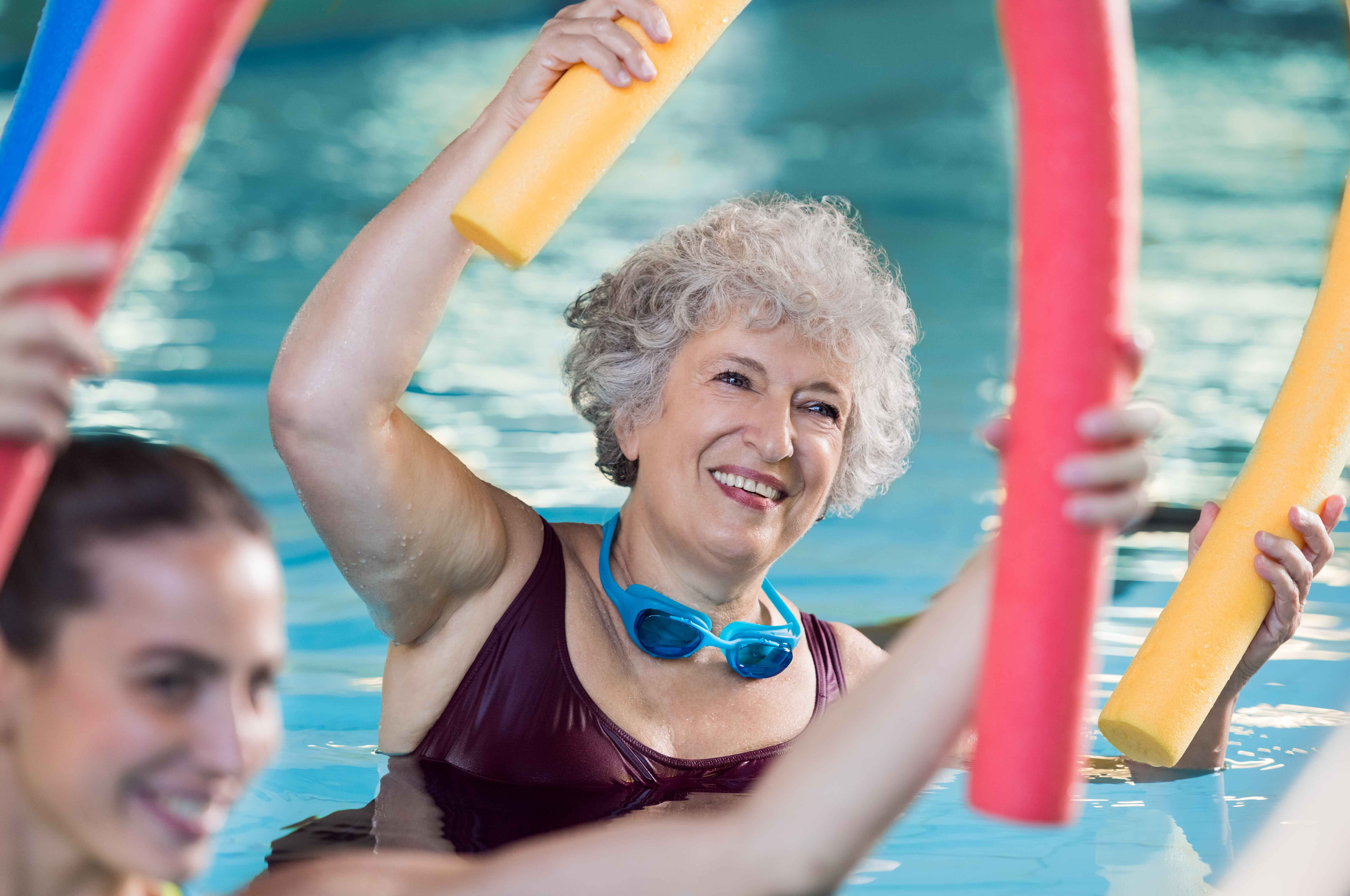 Señora mayor haciendo actividades en una piscina