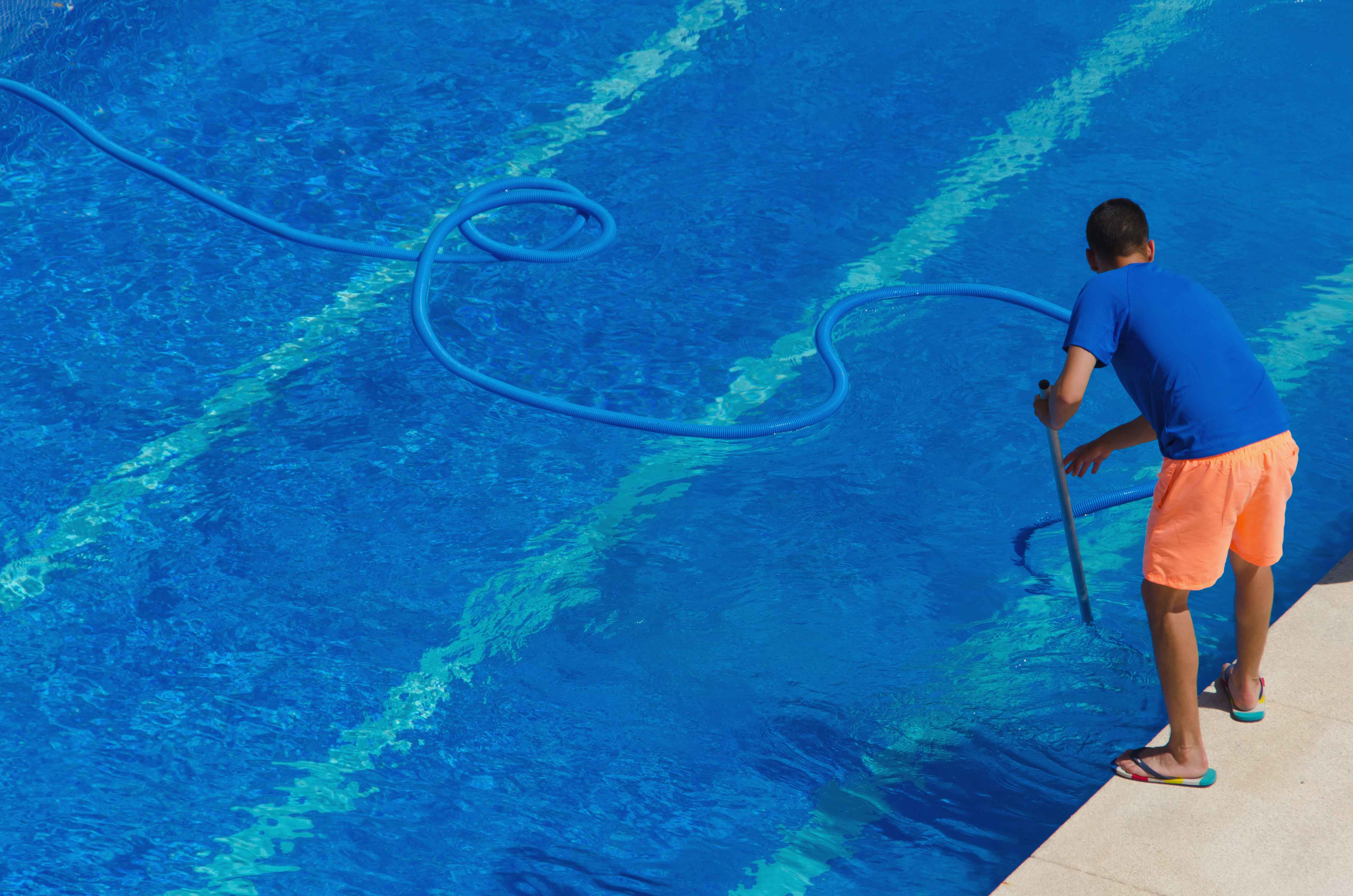 Chico limpiando piscina