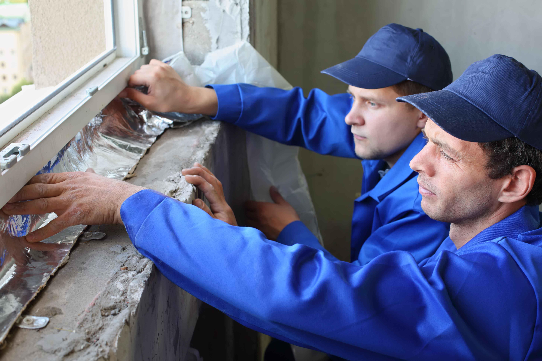 Dos trabajadores colocando aislamiento térmico a ventana