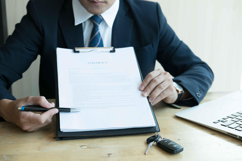 Ejecutivo con un contrato en la mano dándolo a firmar