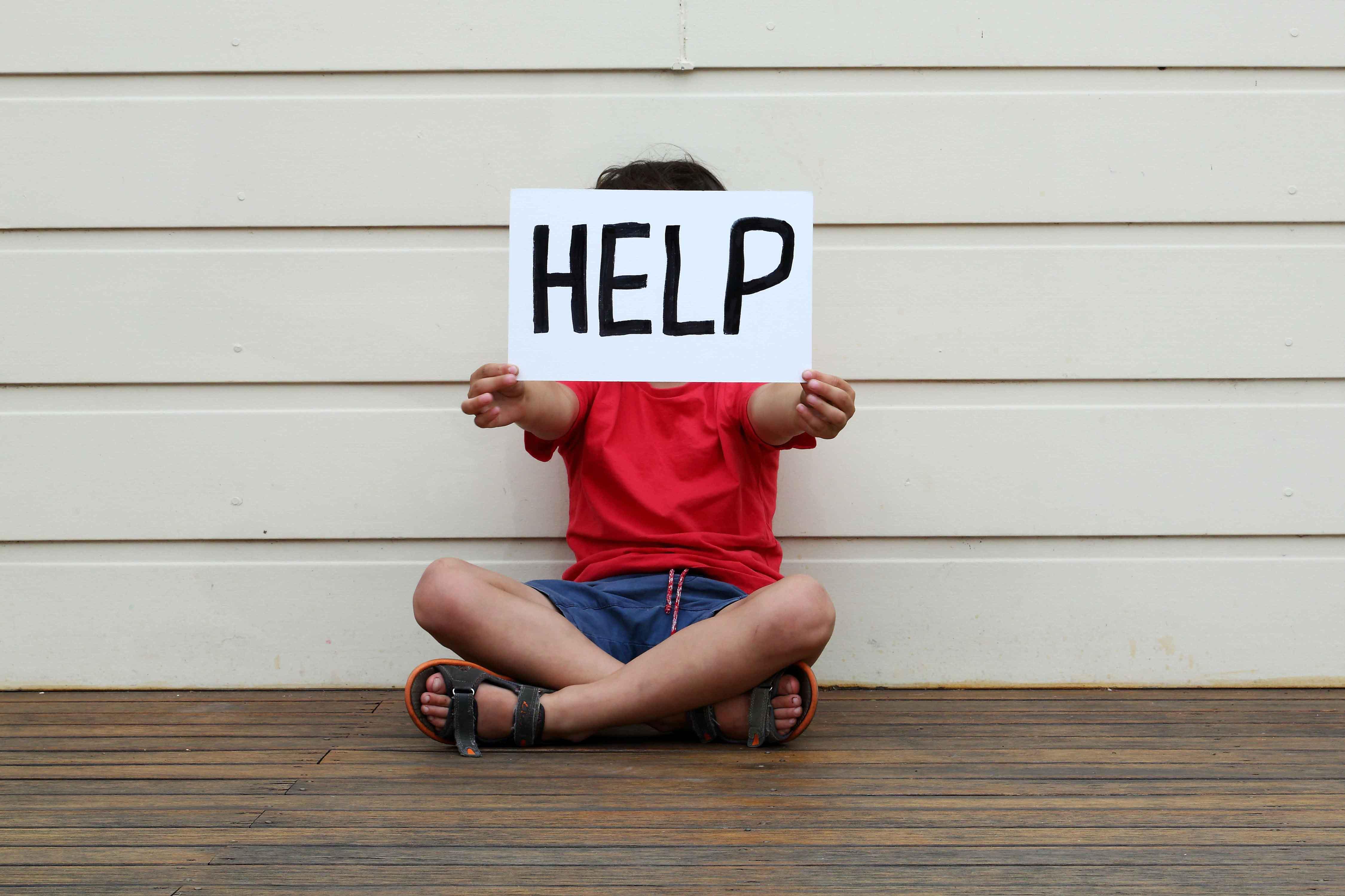 """Niño sujetando a la altura de la cara cartel con mensaje """"ayuda"""""""