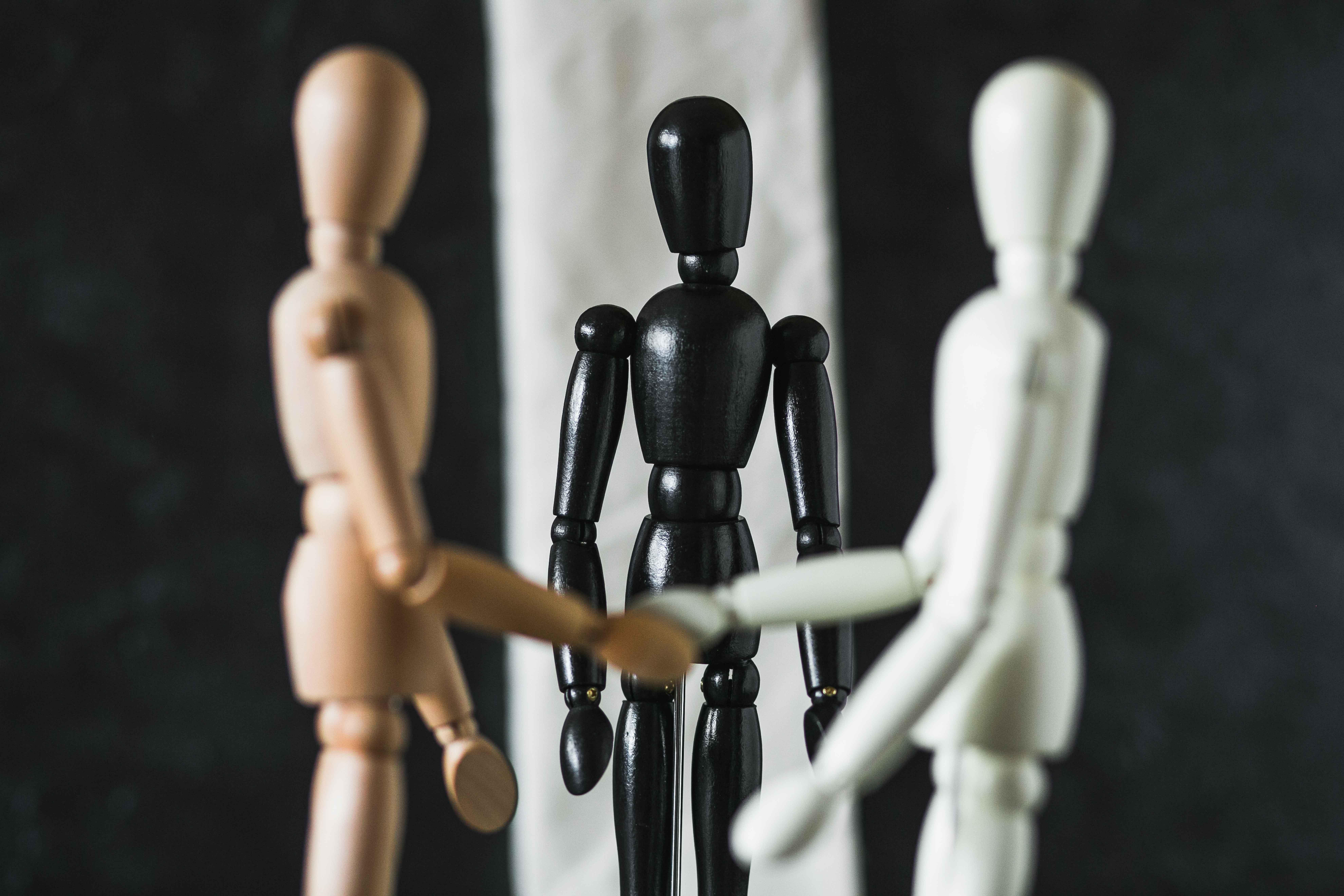 Figuras de madera de colores diferentes dándose la mano