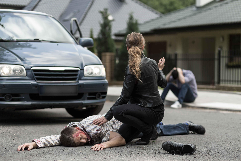 Chica atendiendo a víctima de accidente en el suelo con otra víctima de fondo