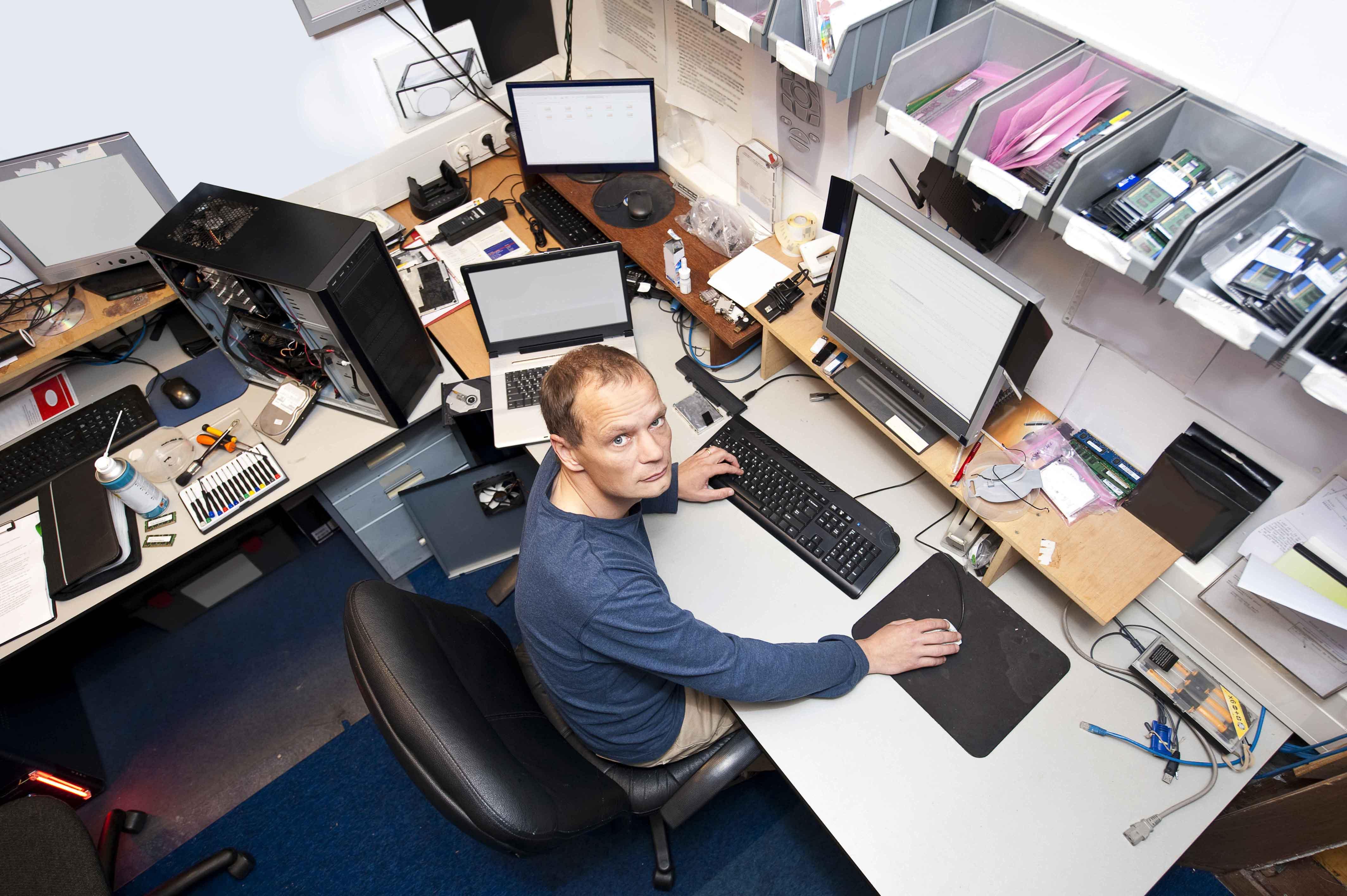 Chico trabajando en ordenador rodeado de piezas informáticas