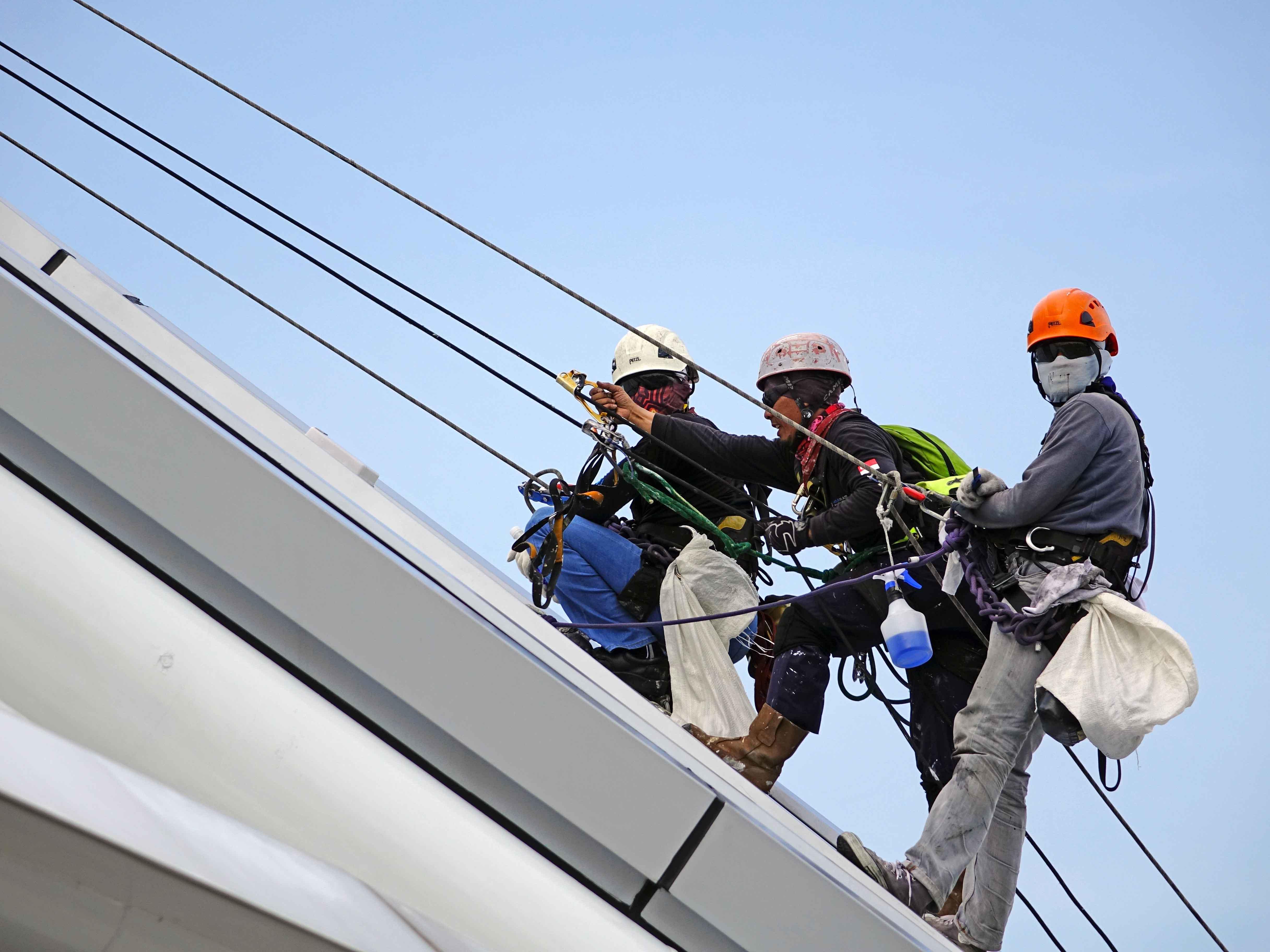obreros colgados de arnés en fachada de edificio