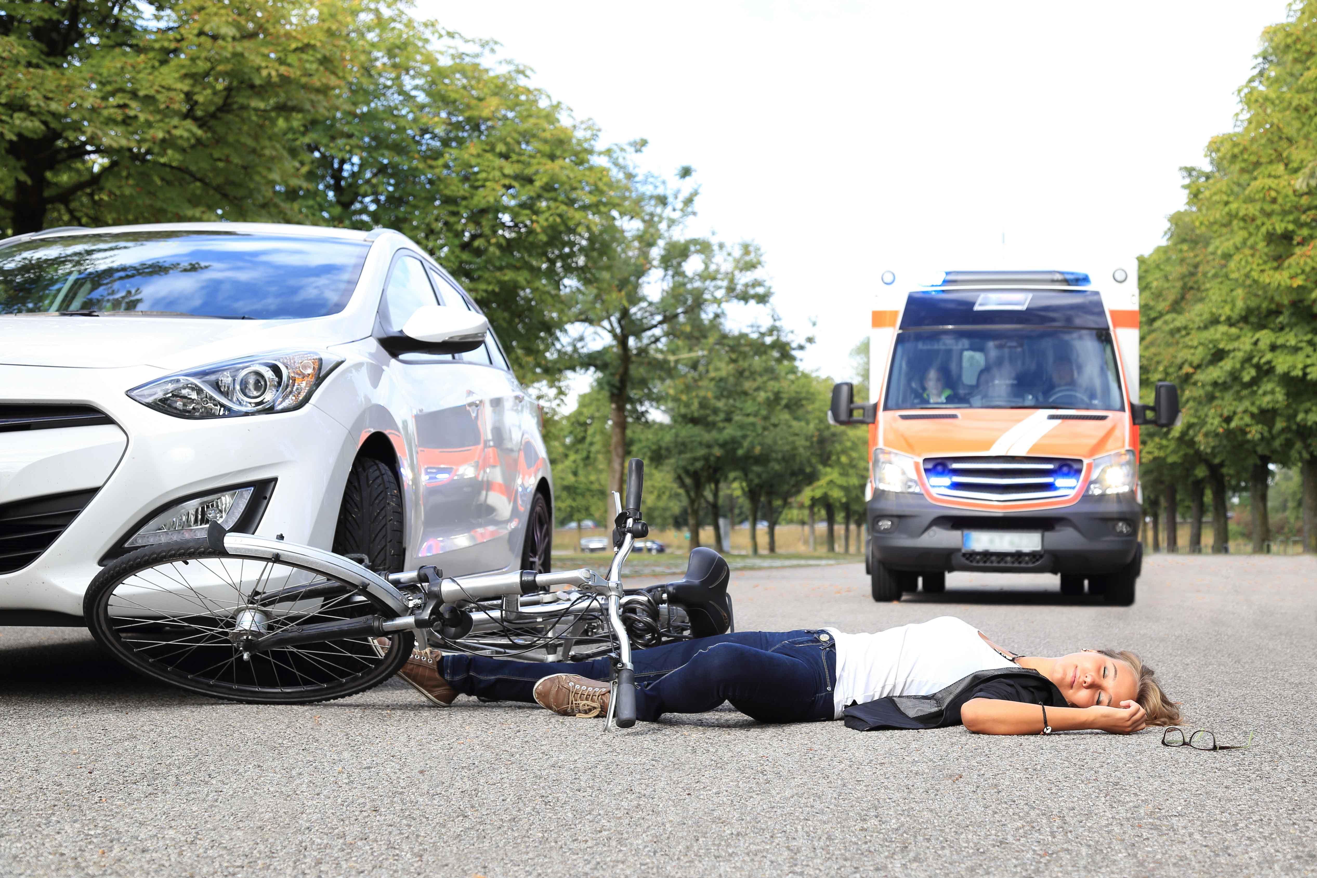 Ambulancia llegando a lugar de accidente con mujertendida en el suelo