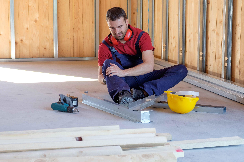 Obrero doliéndose de una pierna tras accidente laboral