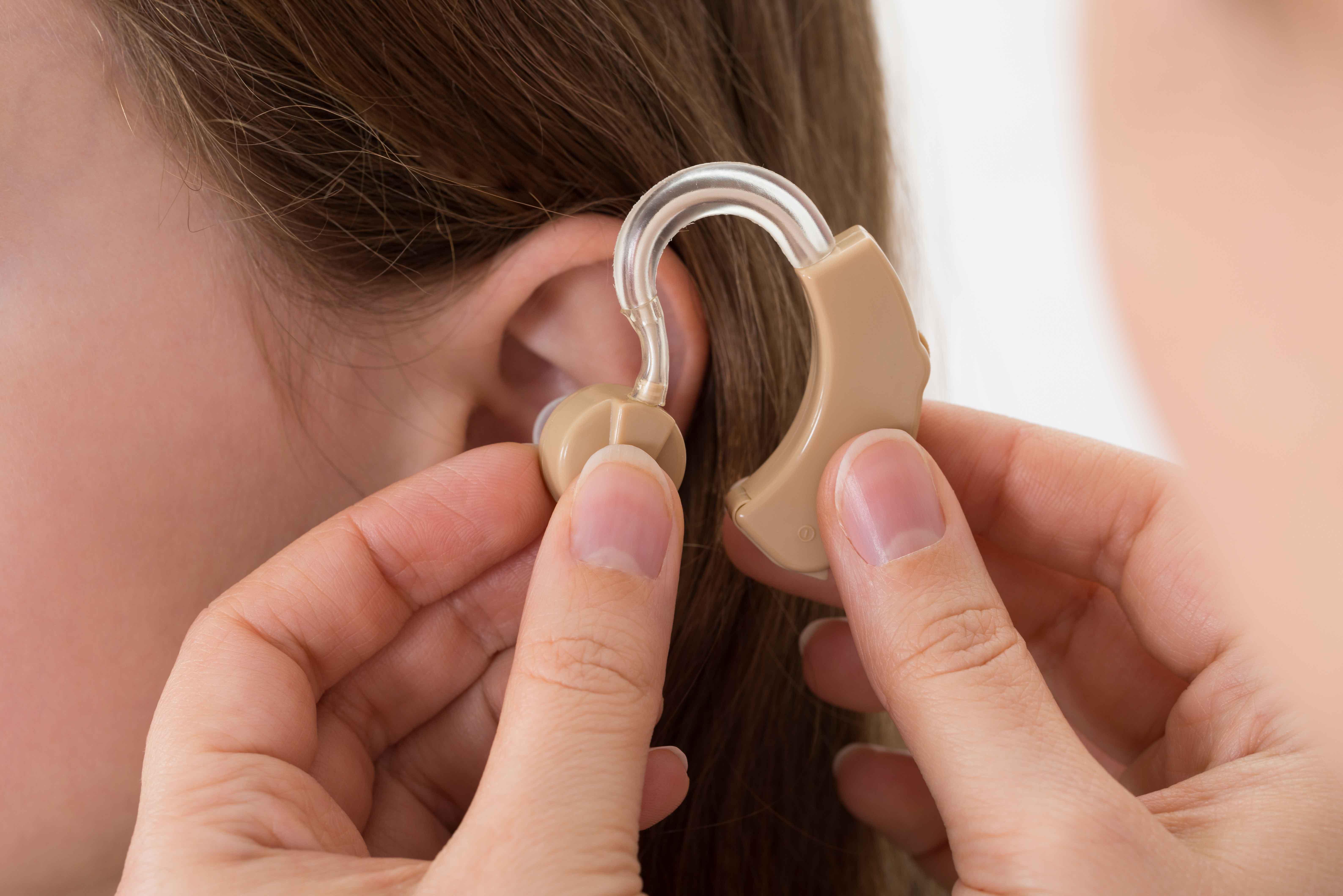Chica poniéndose prótesis en oreja