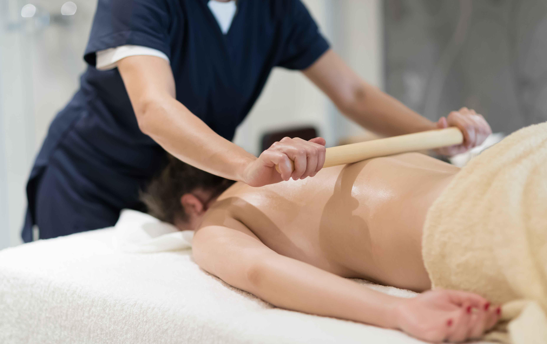 Chica dando masaje utilizando un rodillo