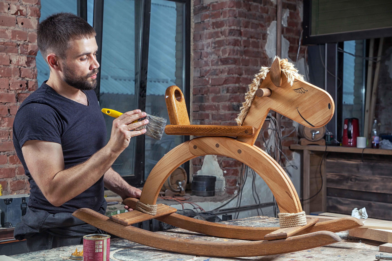 Chico trabajando reparando caballito de madera de juguete