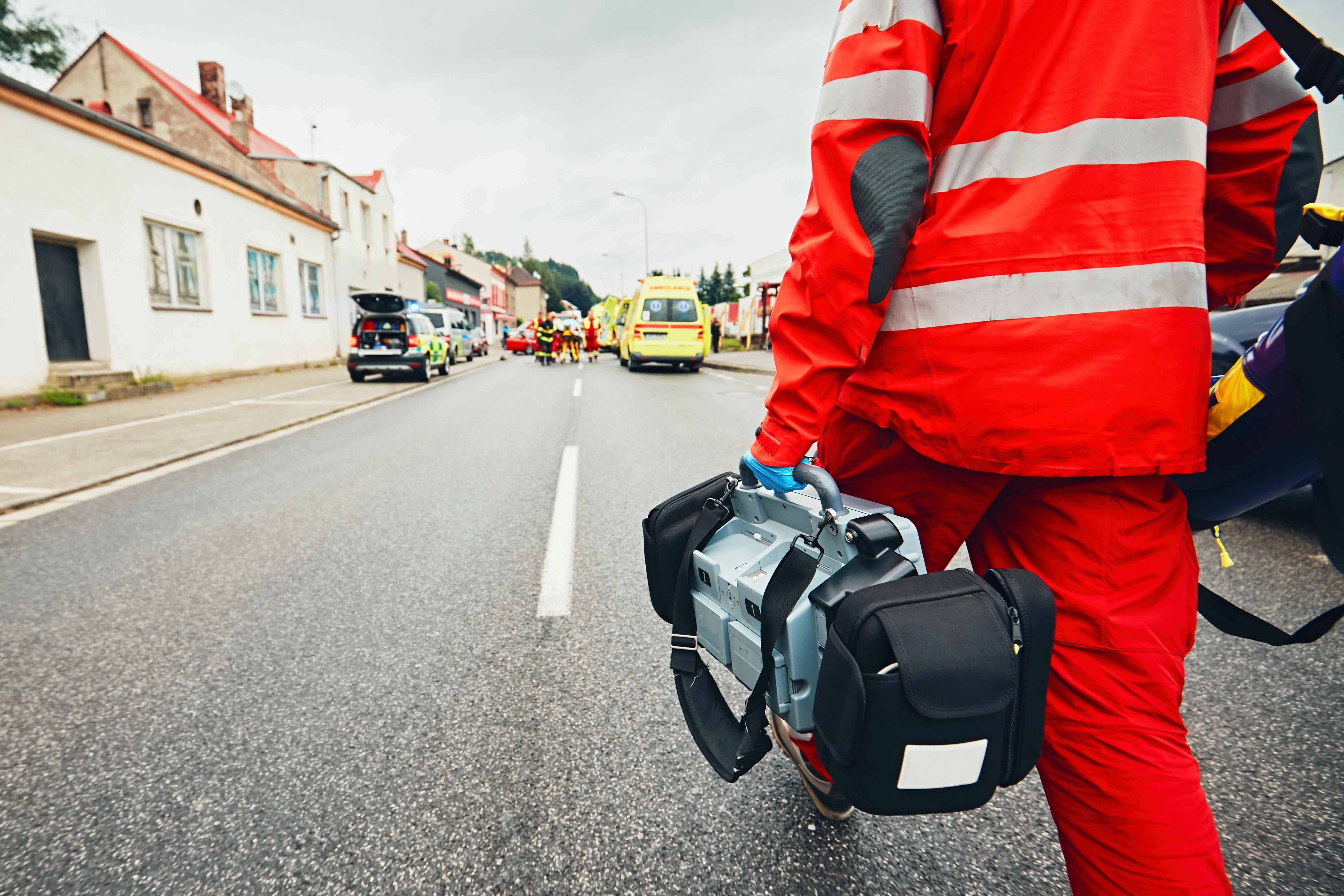 Técnico con maletín de material y ambulancias al fondo