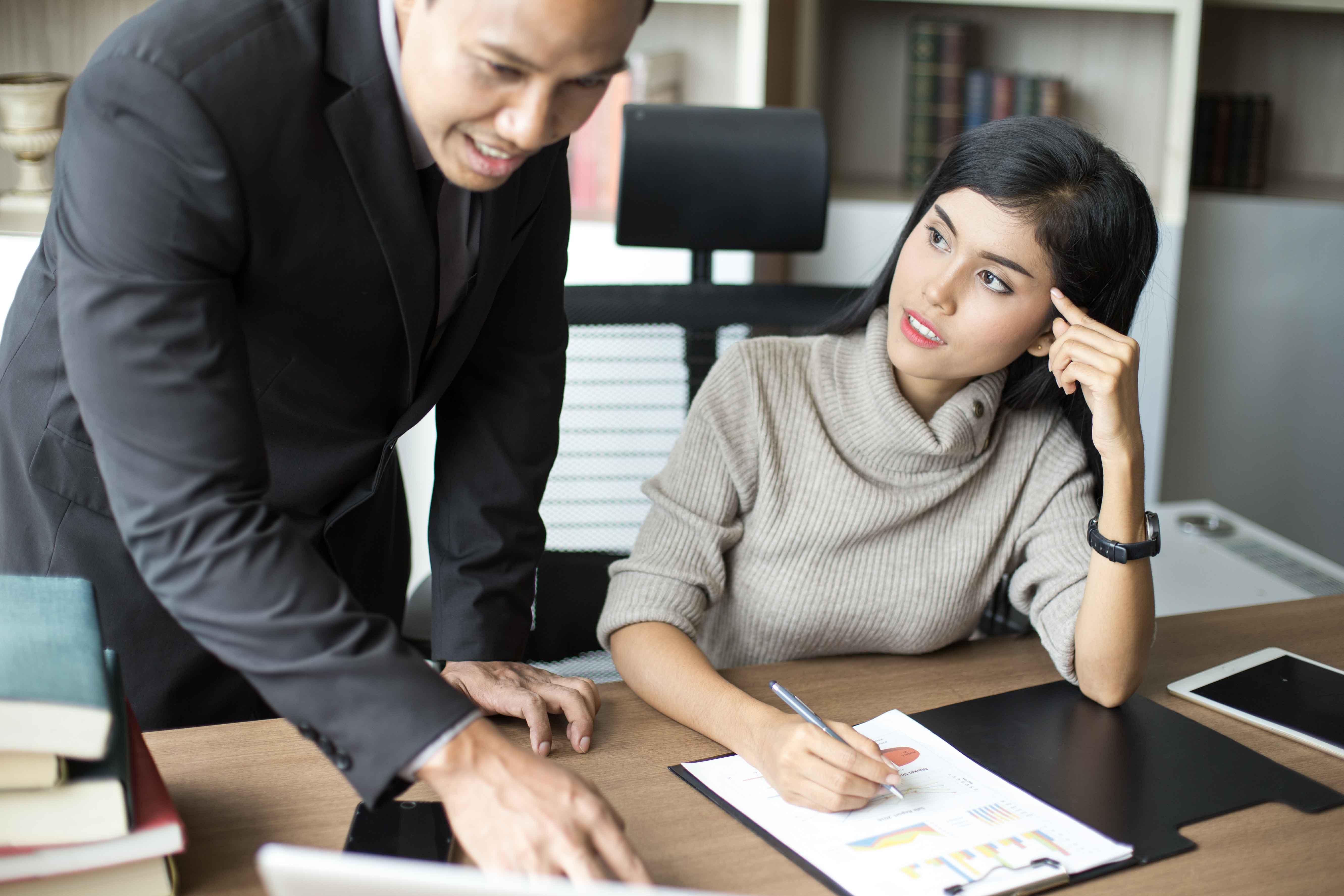 Ejecutiva y secretario charlando en un despacho