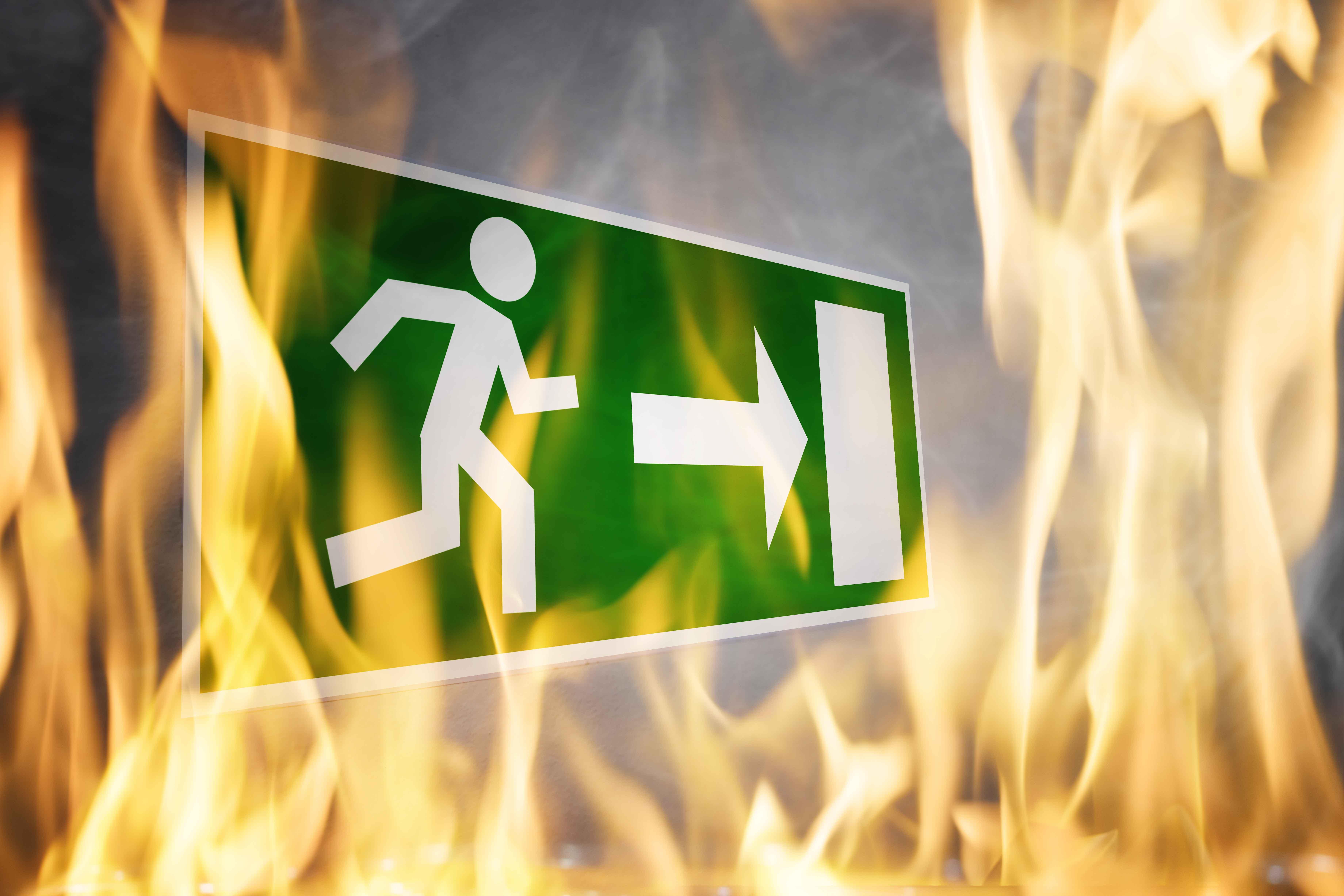 Cartel de salida de emergencia rodeado de llamas