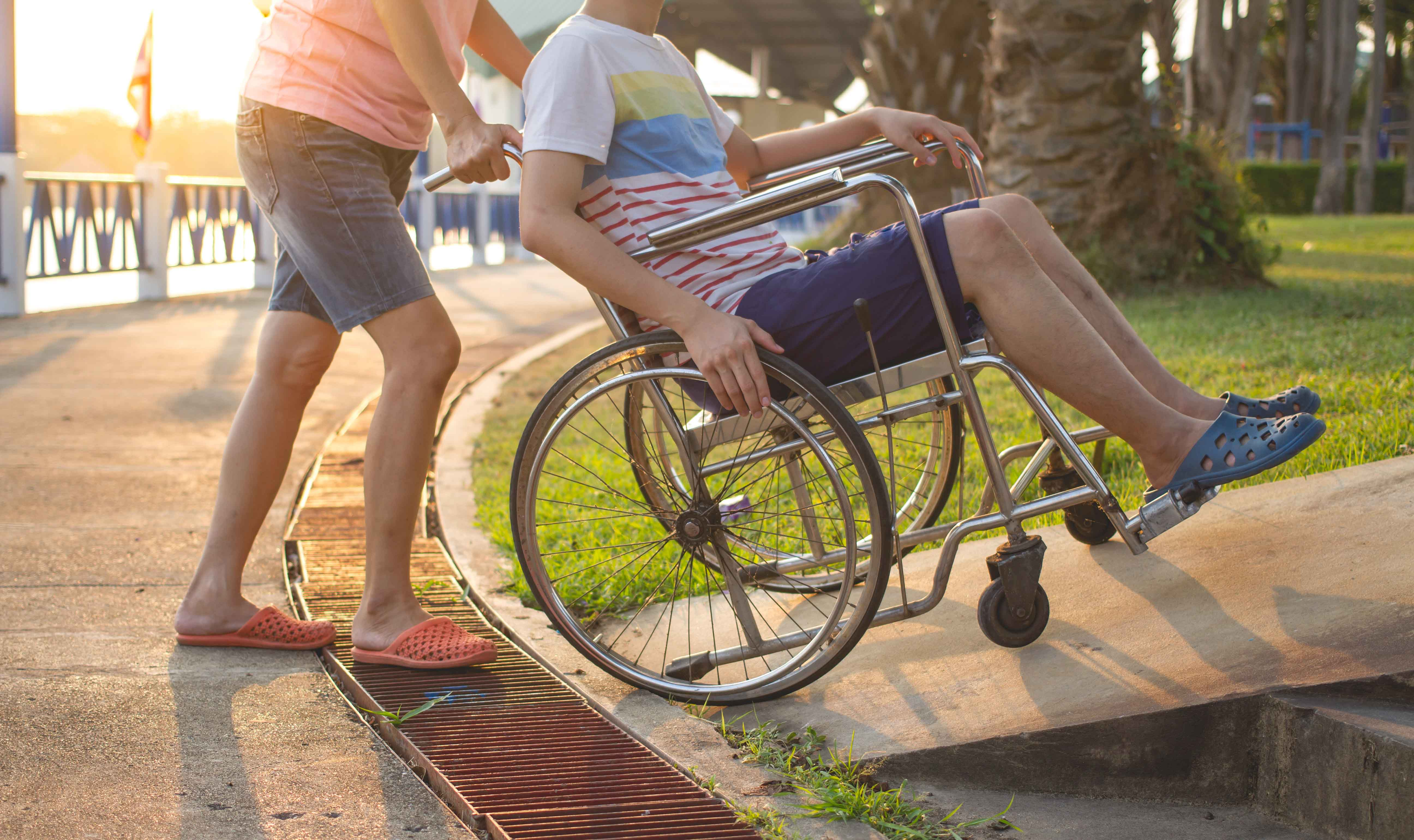 Mujer ayudando a chico en silla de ruedas a subir una rampa