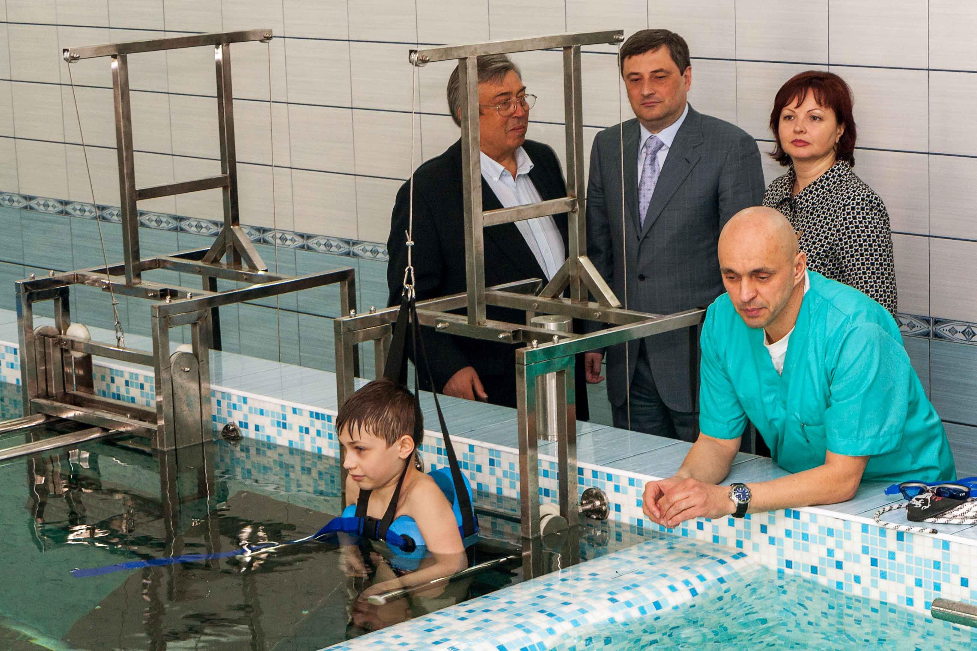 Chico discapacitado rehabilitándose en una piscina