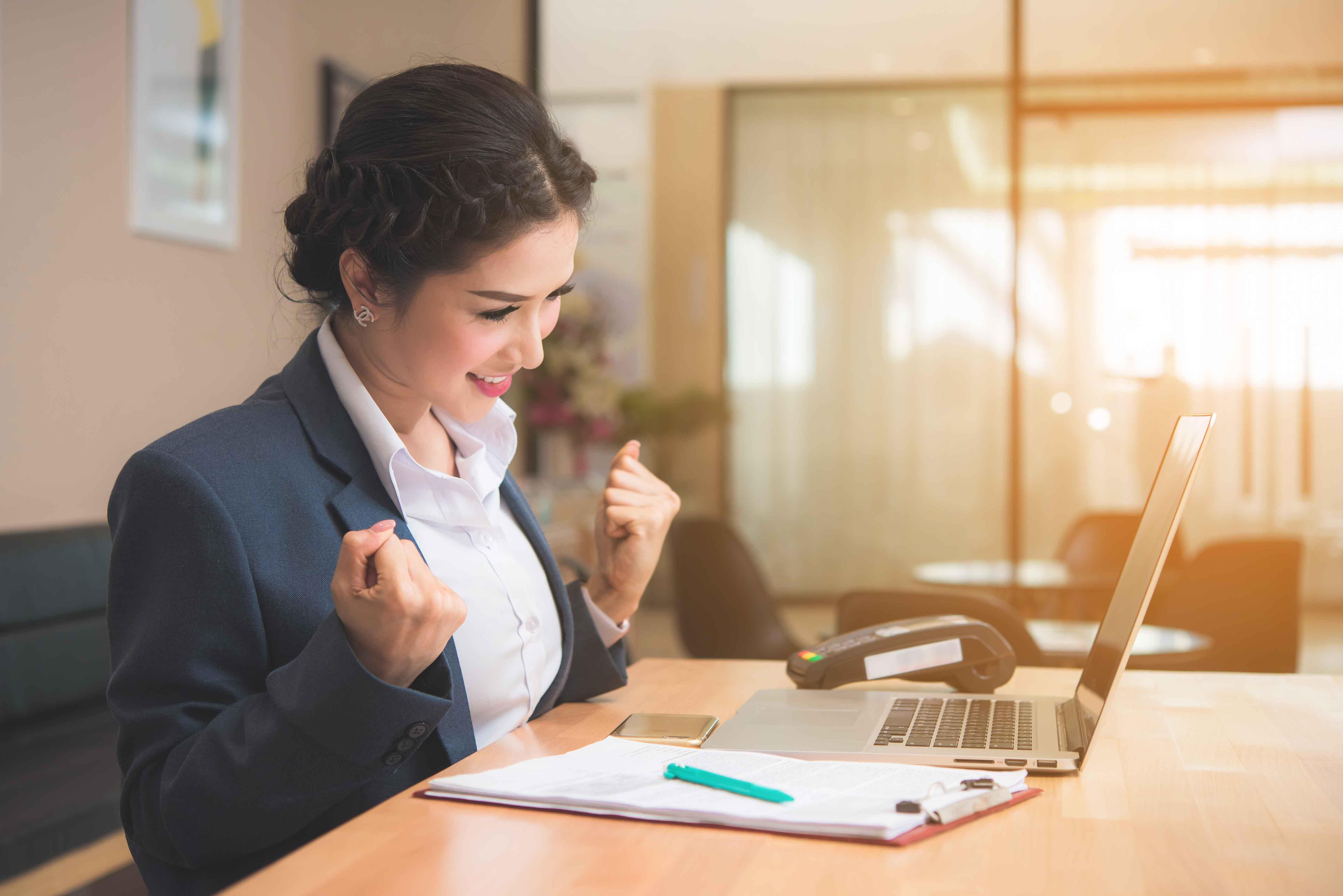 Chica en despacho con gesto de triunfo