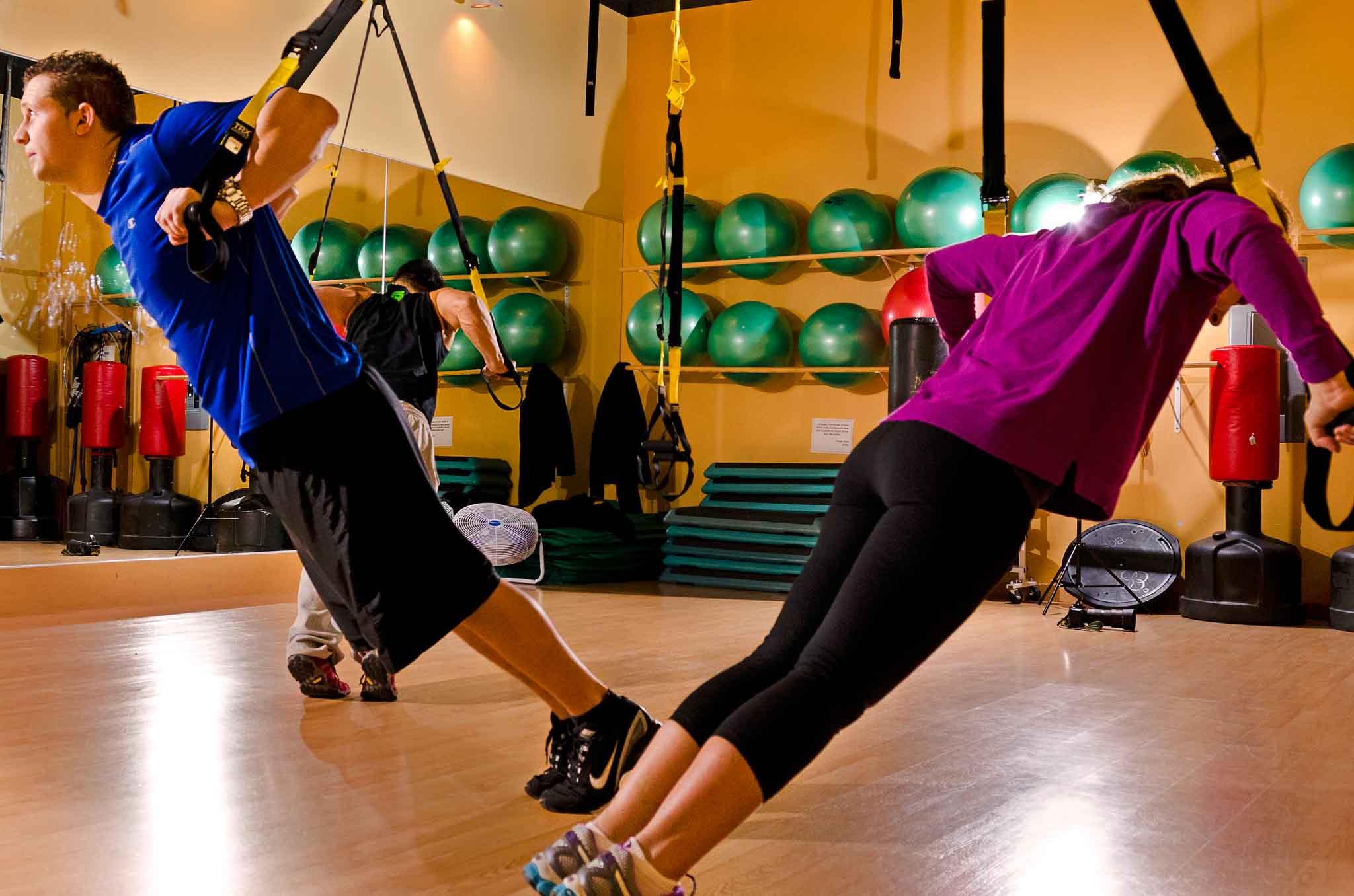 Gente entrenando con cintas TRX en gimnasio