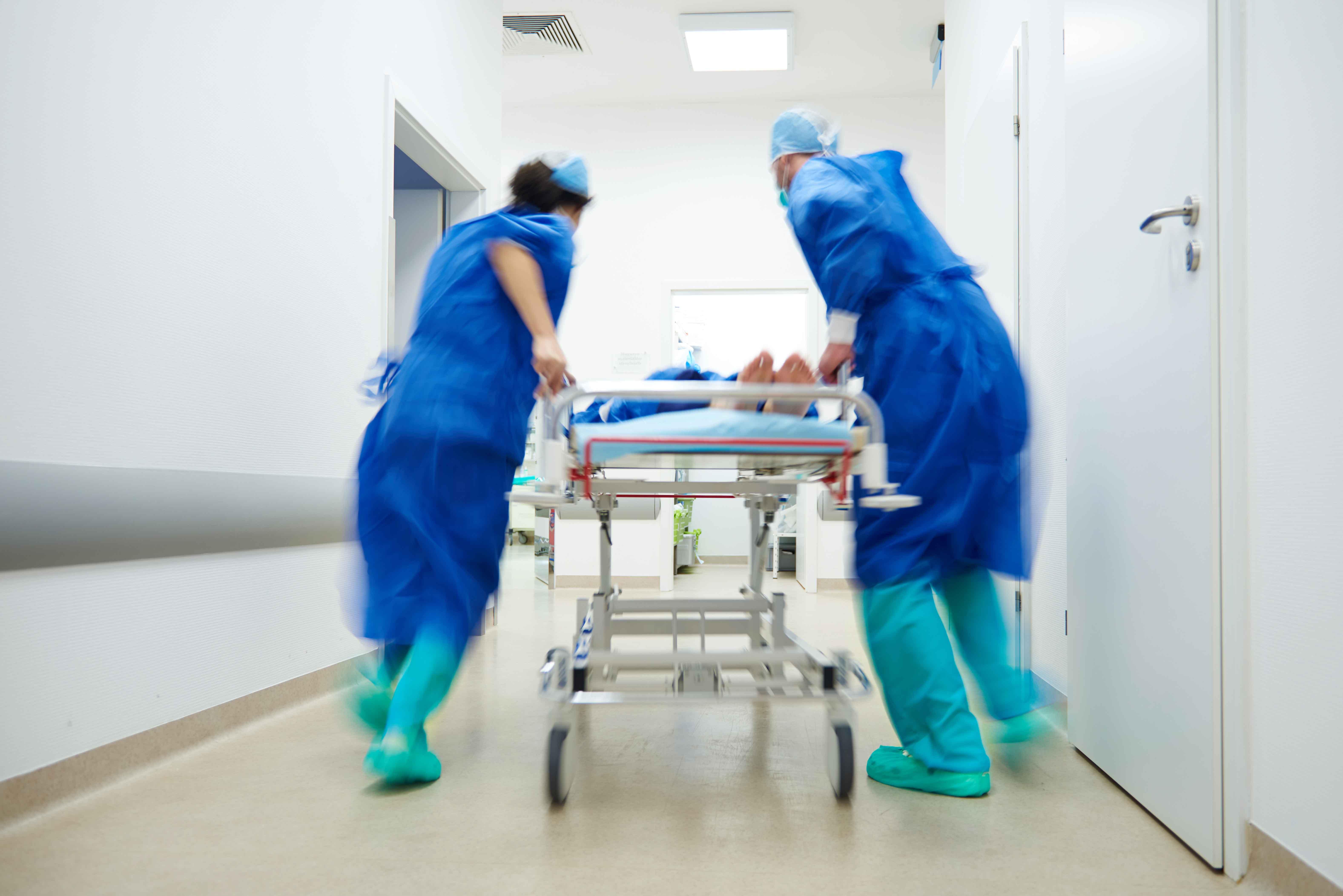 Doctores llevando paciente en camilla por pasillo