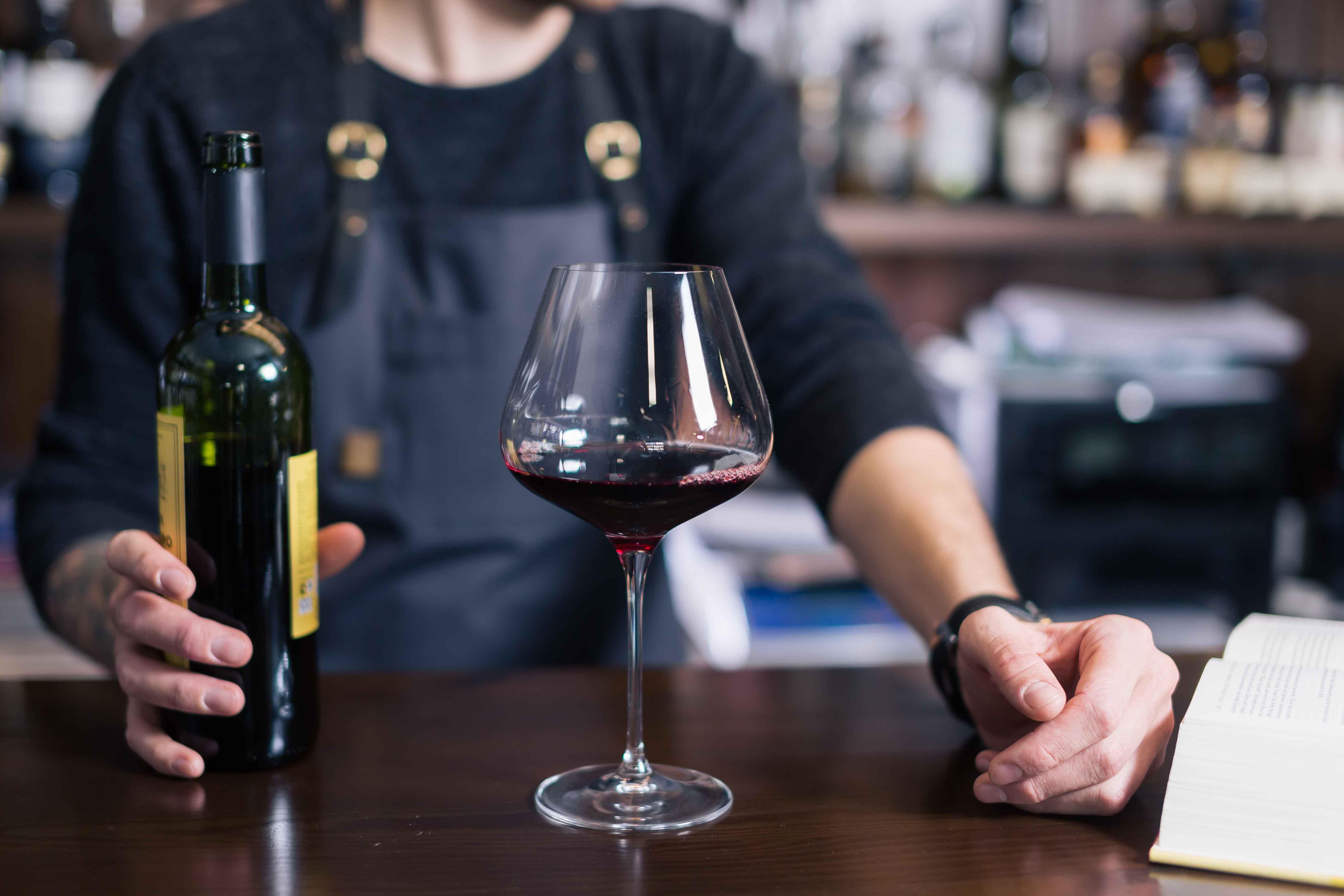Barista sirviendo vino en copa